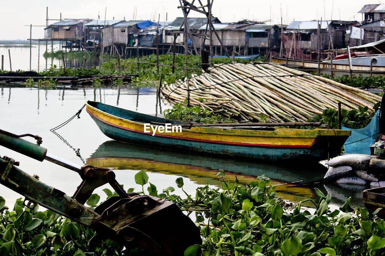 Boat moored in lake against stilt houses
