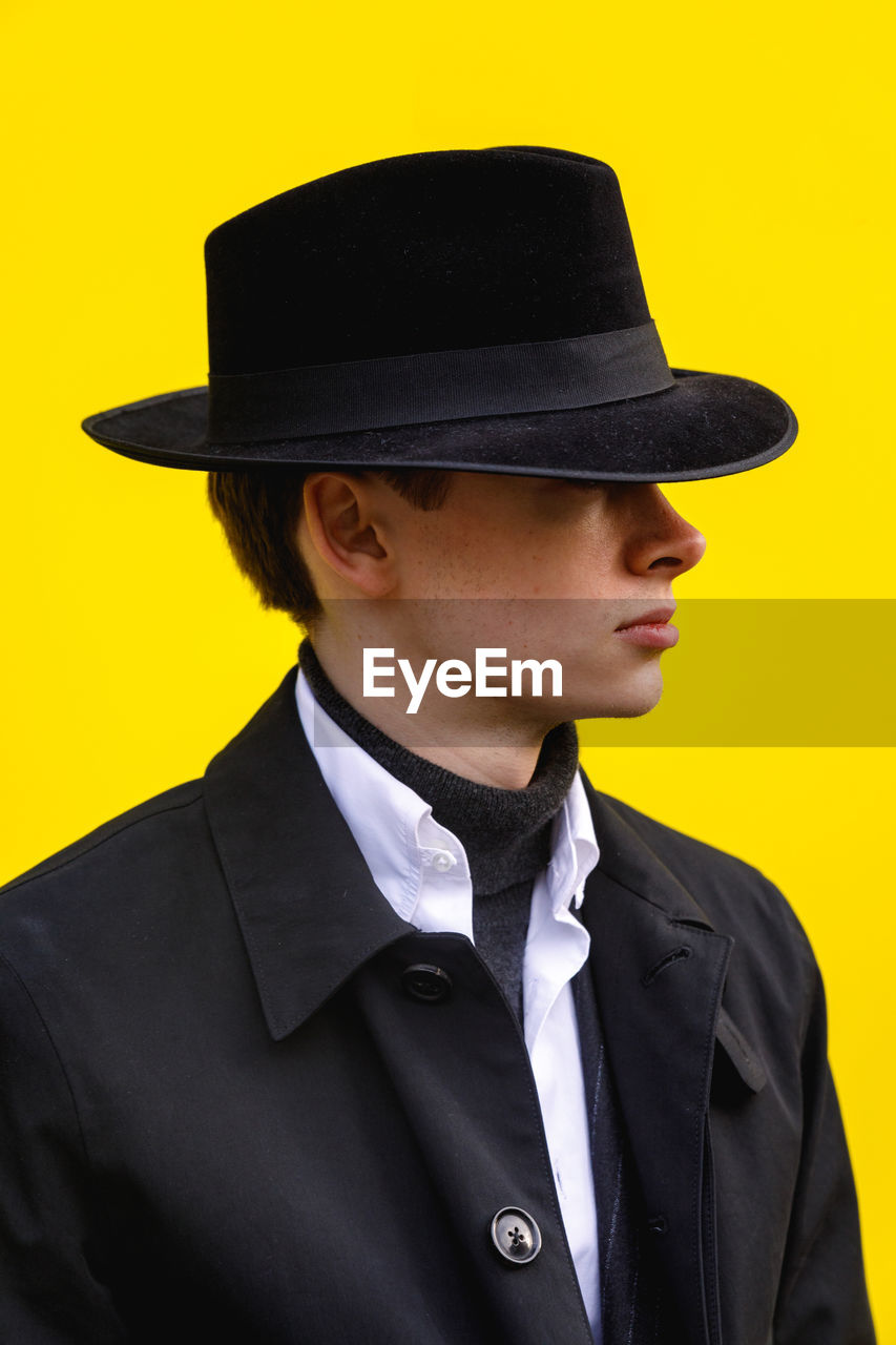 clothing, one person, hat, yellow, studio shot, front view, portrait, indoors, young adult, young men, men, headshot, real people, lifestyles, yellow background, leisure activity, formalwear, suit, well-dressed, menswear, uniform
