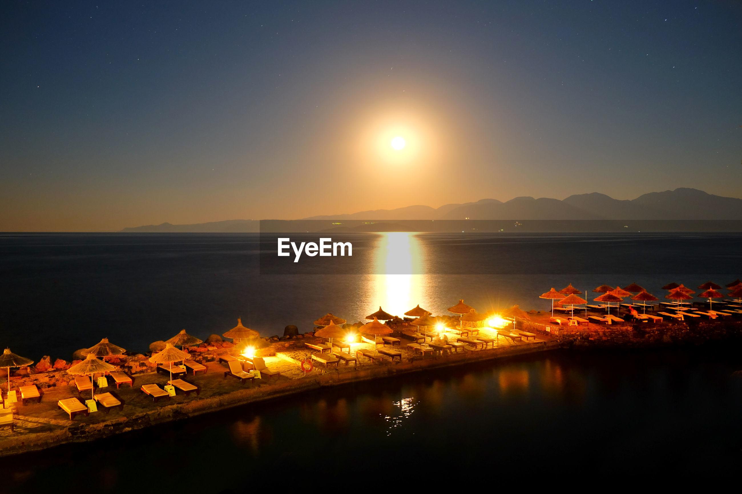 ILLUMINATED SEA AGAINST CLEAR SKY AT NIGHT
