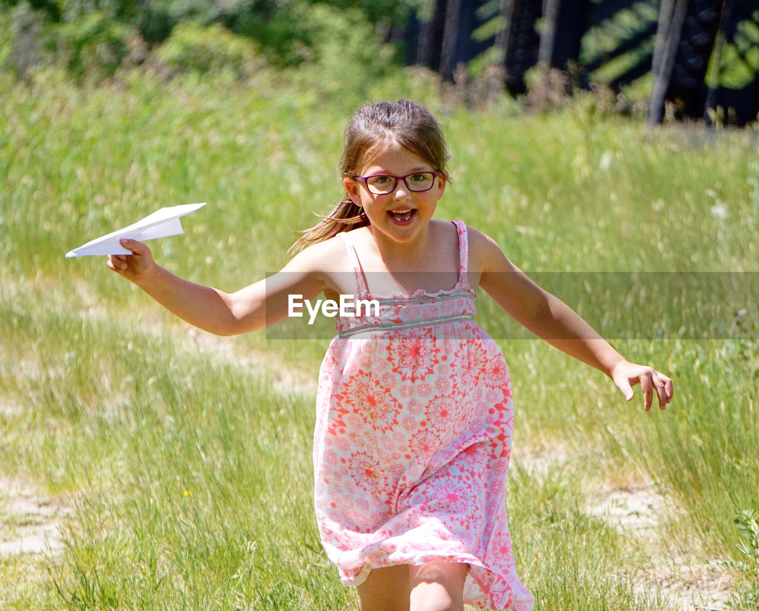 Cheerful girl flying airplane while walking on field during sunny day