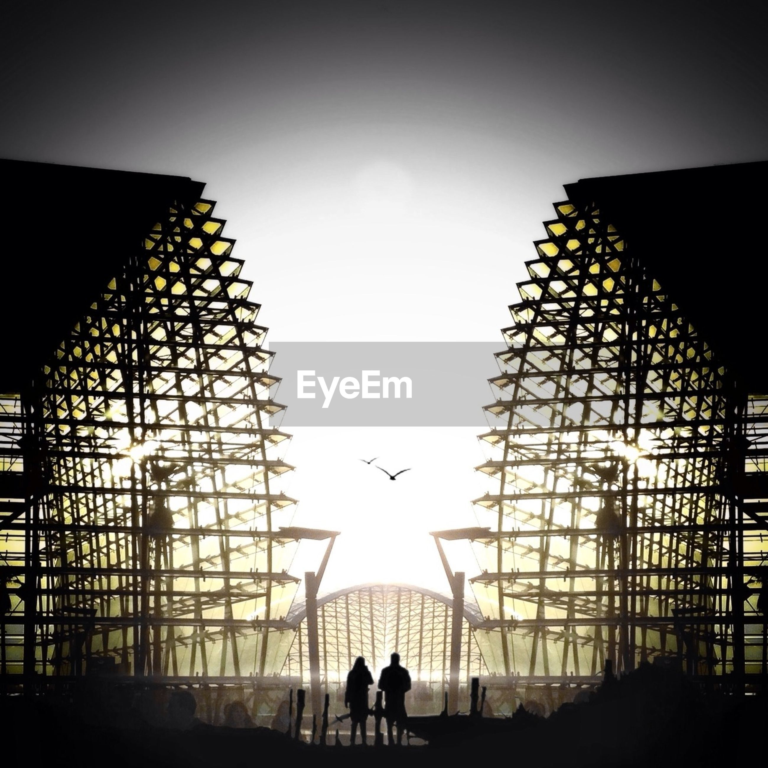 Silhouette people standing by modern built structure against sky