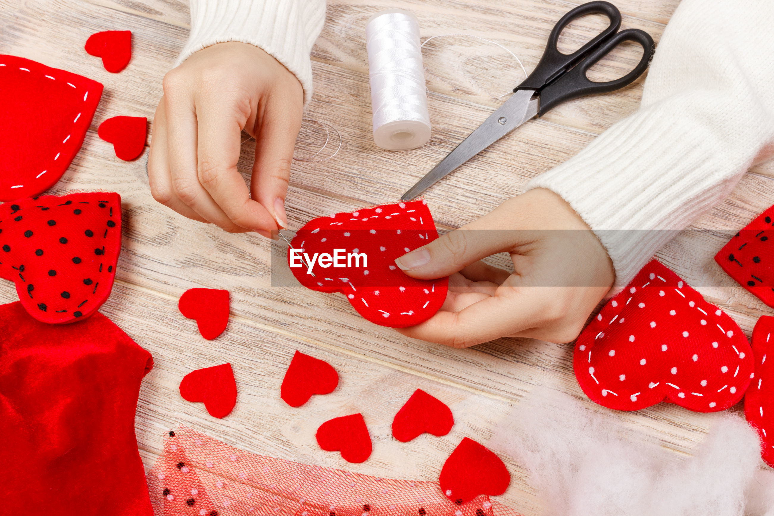 High angle view of woman making felt heart shapes