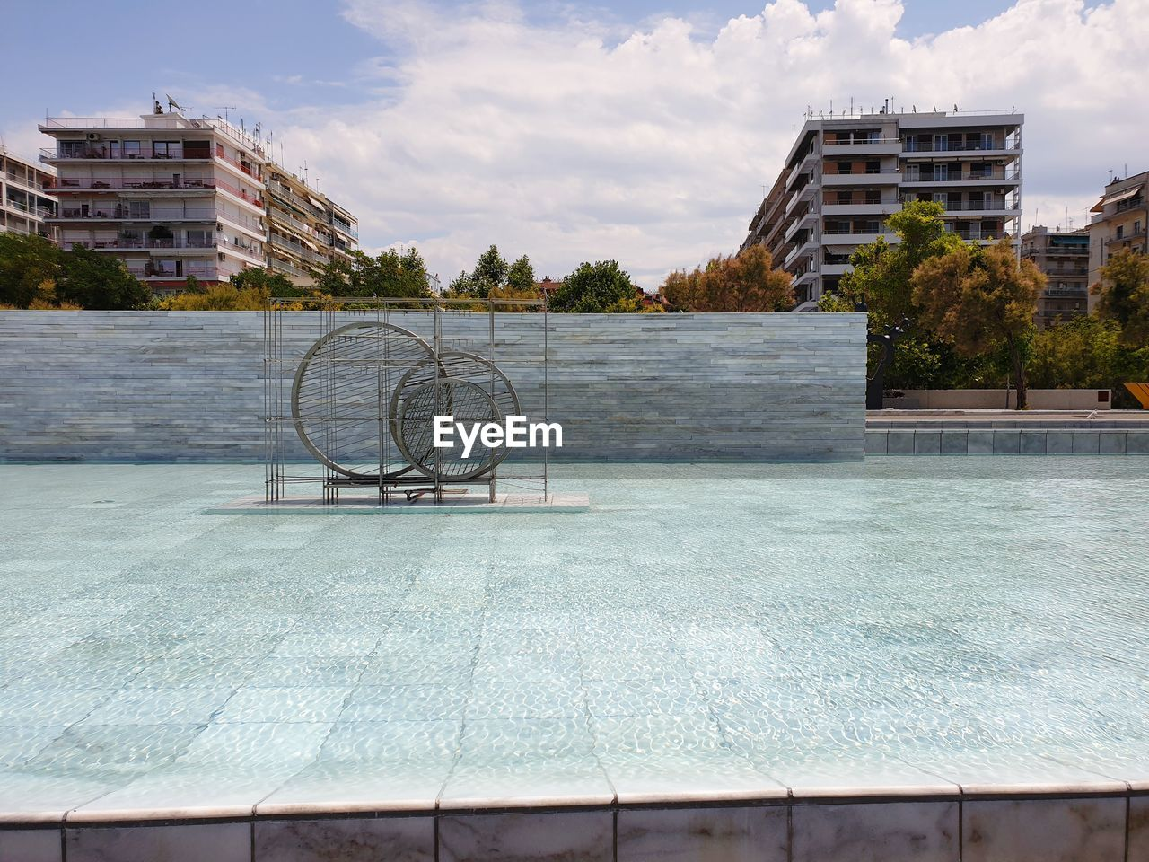 BICYCLE BY SWIMMING POOL AGAINST BUILDING IN CITY