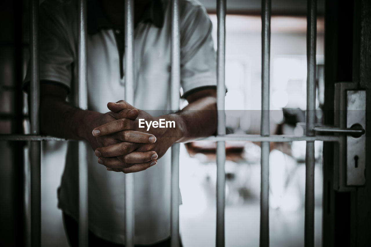 Midsection of man standing in prison