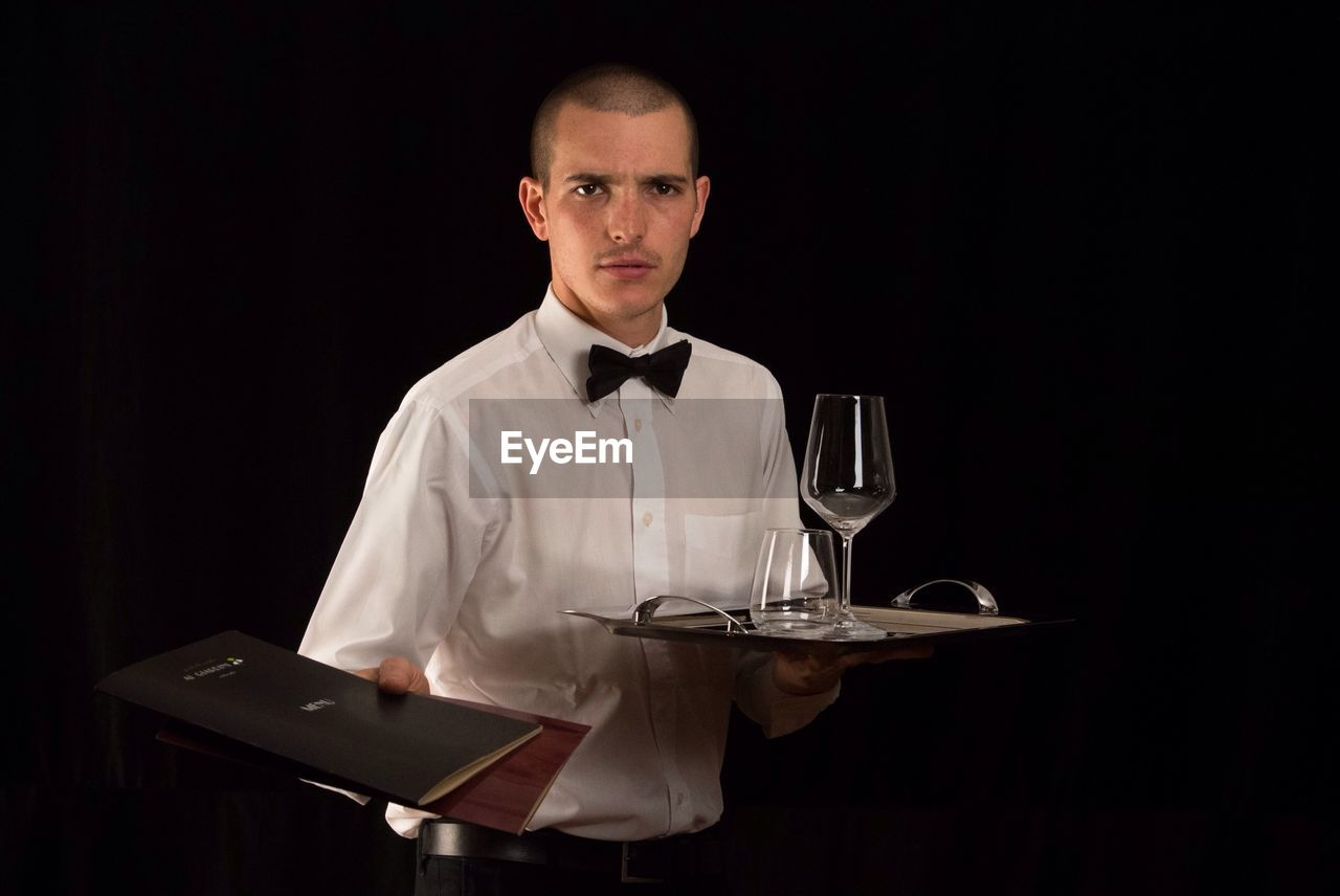 Portrait Of Waiter Holding Tray While Offering Menu Over Black Background