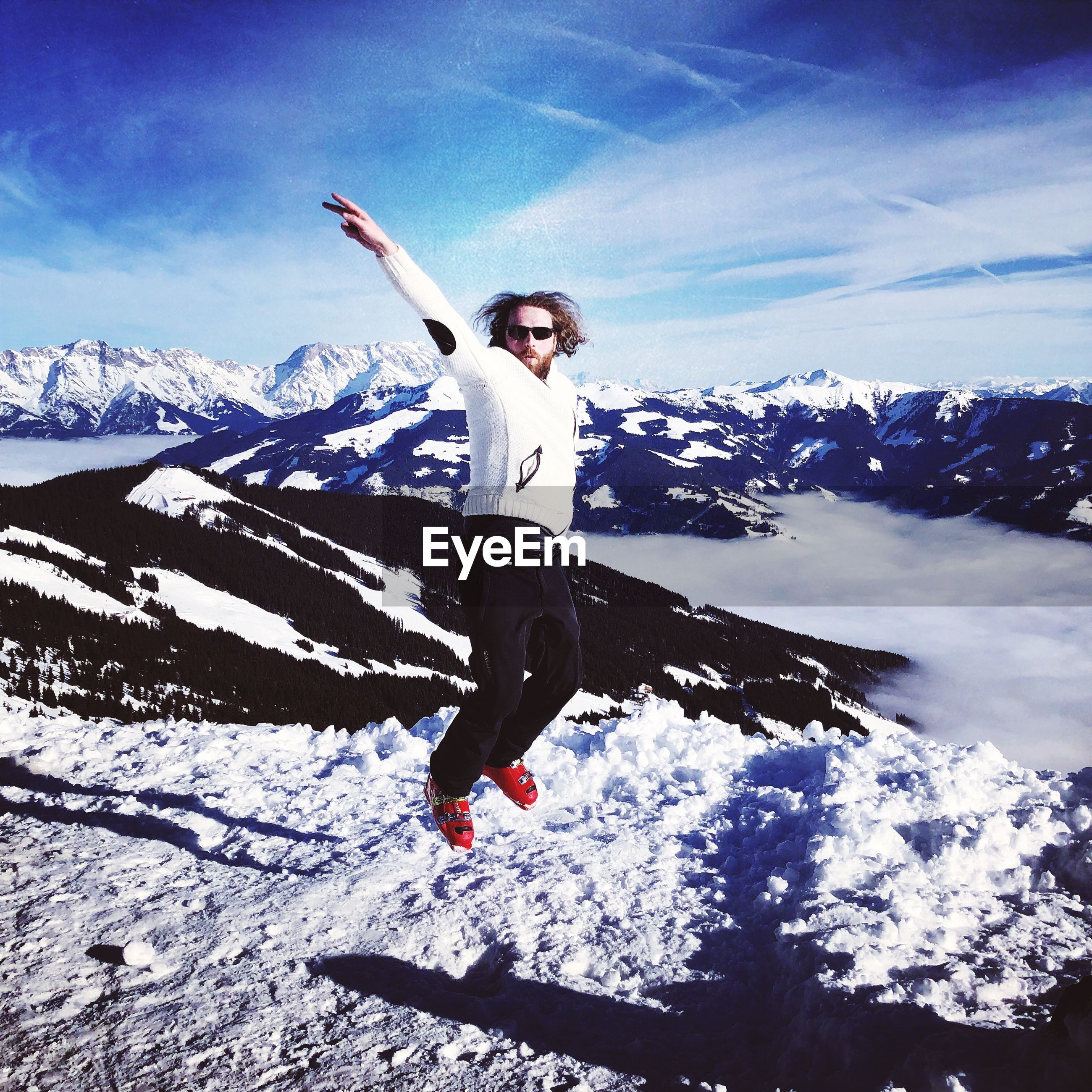 Portrait of mid adult man jumping on snow covered mountain