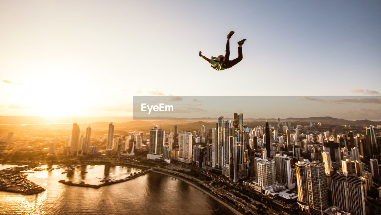 Man Paragliding In Mid-Air In City At Sunset