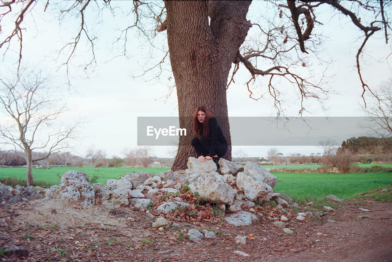 Portrait of young woman sitting on rocks against trees