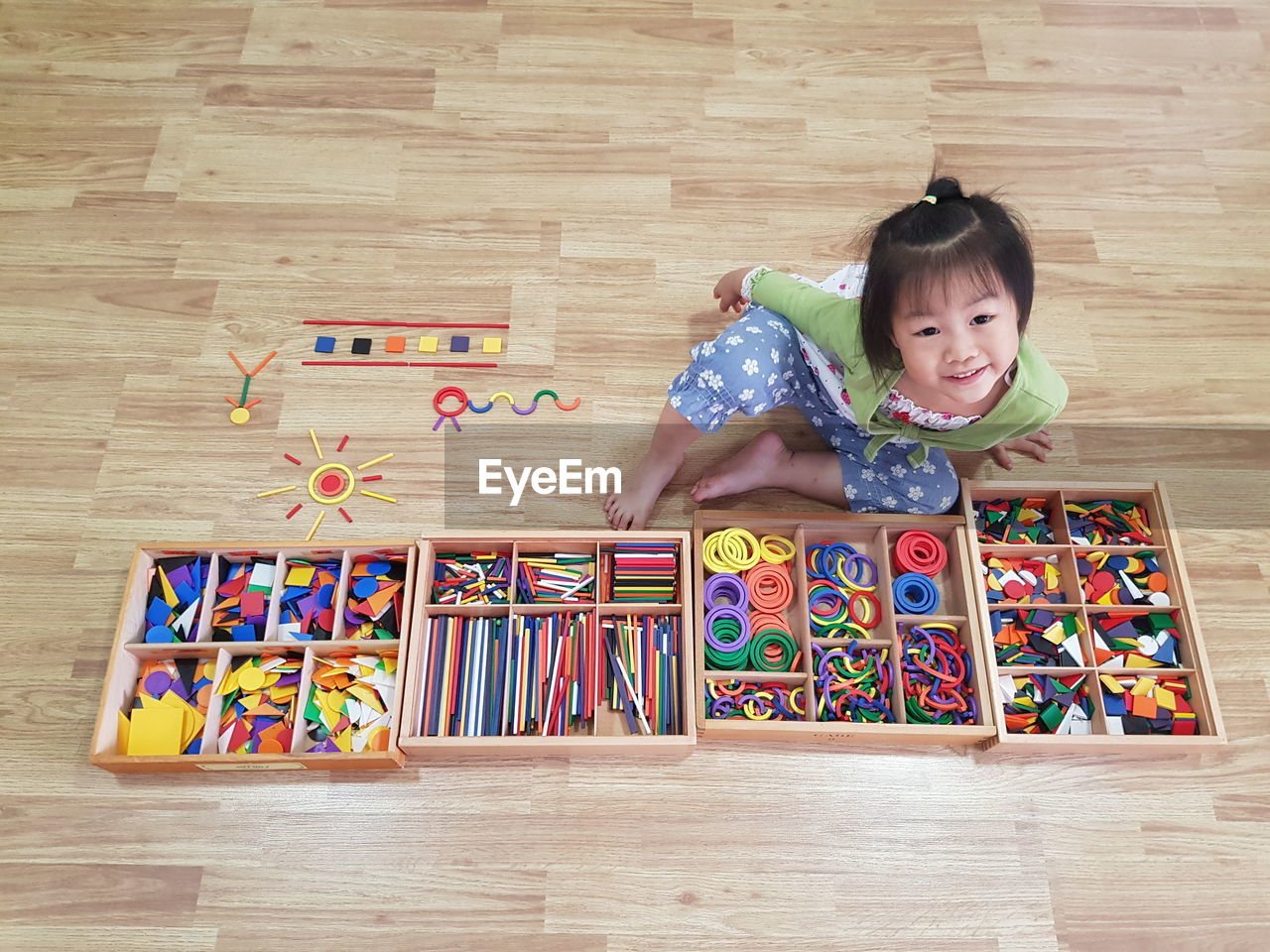 childhood, indoors, child, portrait, front view, multi colored, smiling, emotion, high angle view, flooring, one person, toy, innocence, leisure activity, wood, hardwood floor, girls, happiness, looking at camera, cute, positive emotion
