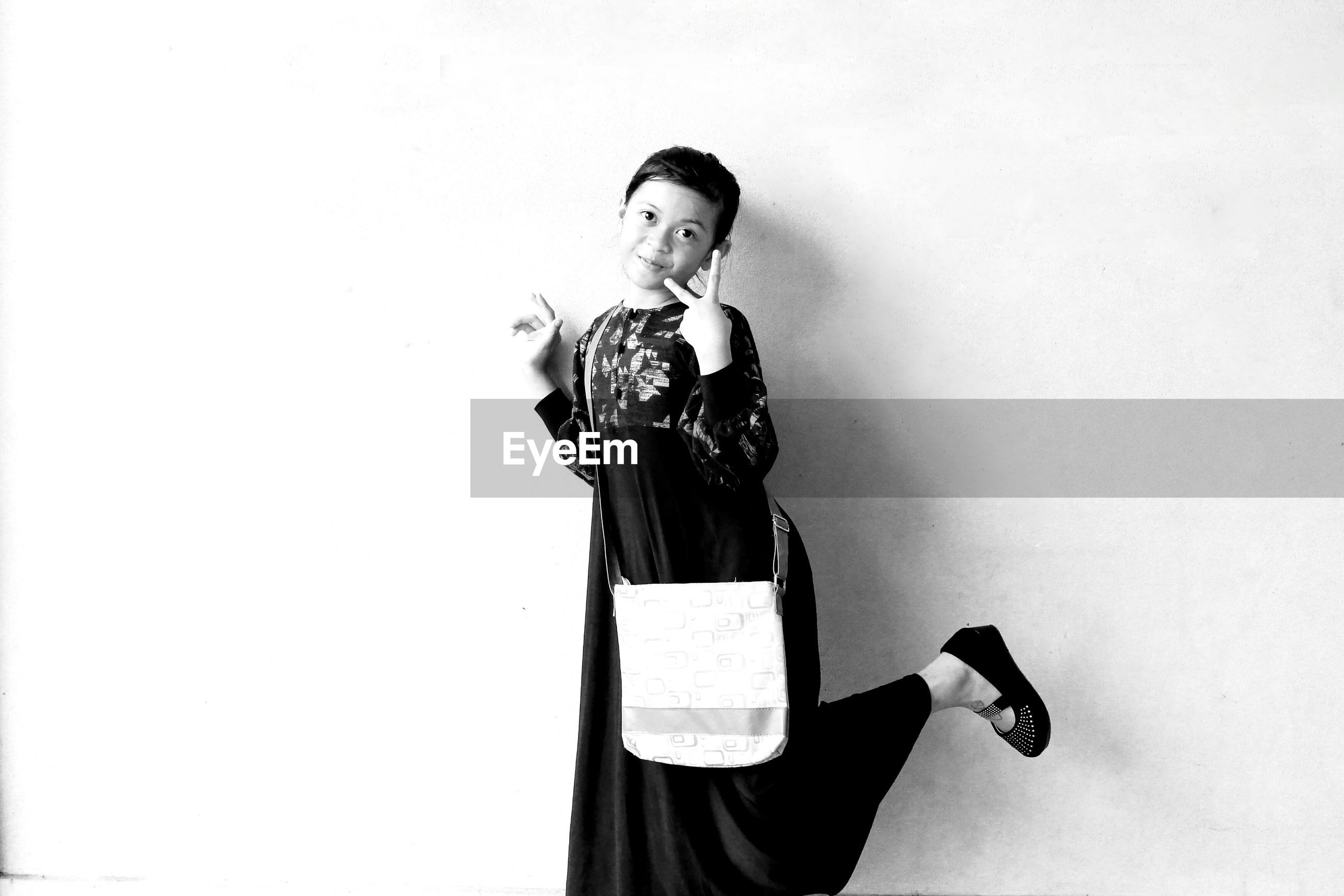Portrait of girl showing peace sign while standing against wall