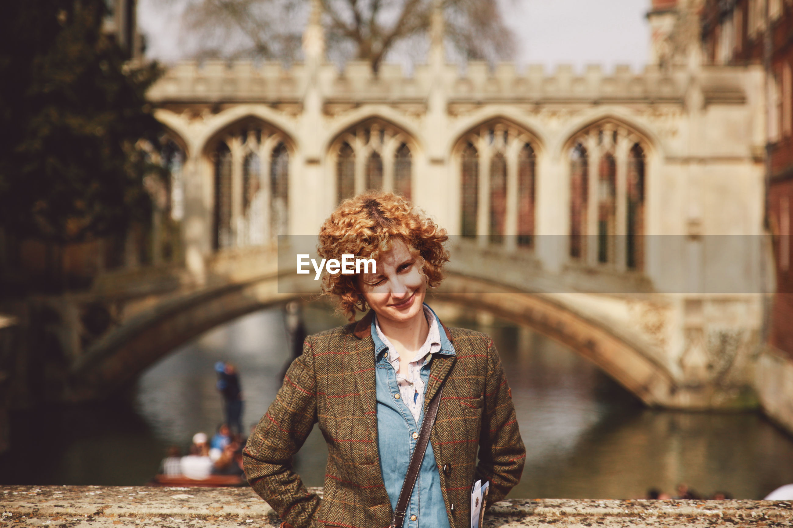 Portrait of woman winking while standing on bridge over canal