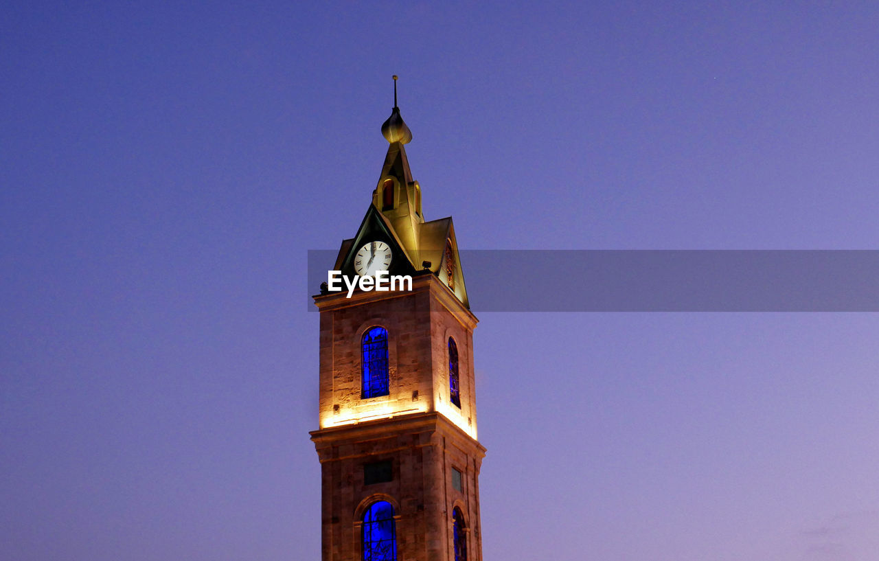 tower, built structure, building exterior, architecture, building, sky, low angle view, religion, clear sky, place of worship, spirituality, belief, copy space, blue, no people, nature, clock tower, time, spire, clock, tall - high, outdoors, purple