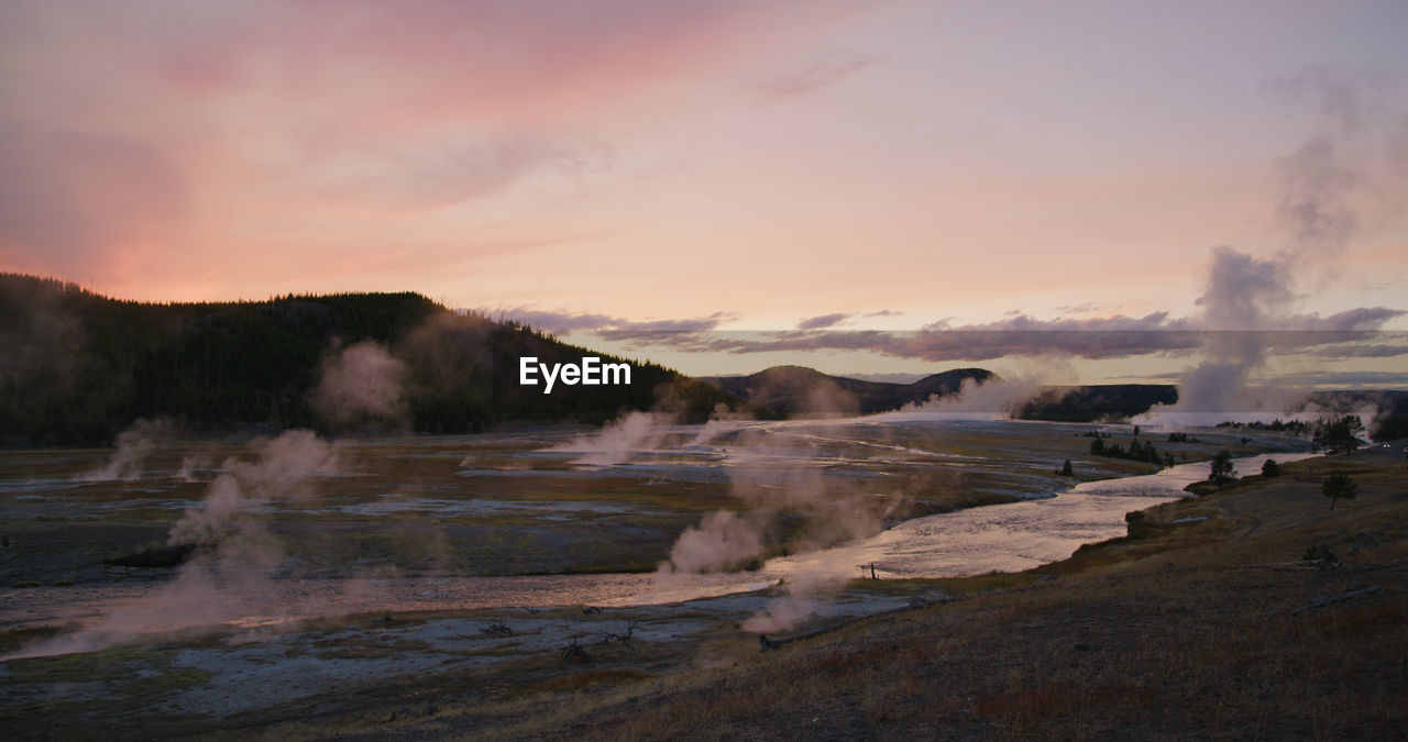 sky, scenics - nature, smoke - physical structure, beauty in nature, sunset, geology, water, geyser, environment, landscape, hot spring, steam, nature, power in nature, non-urban scene, physical geography, erupting, tranquil scene, heat - temperature, no people, emitting, outdoors, pollution