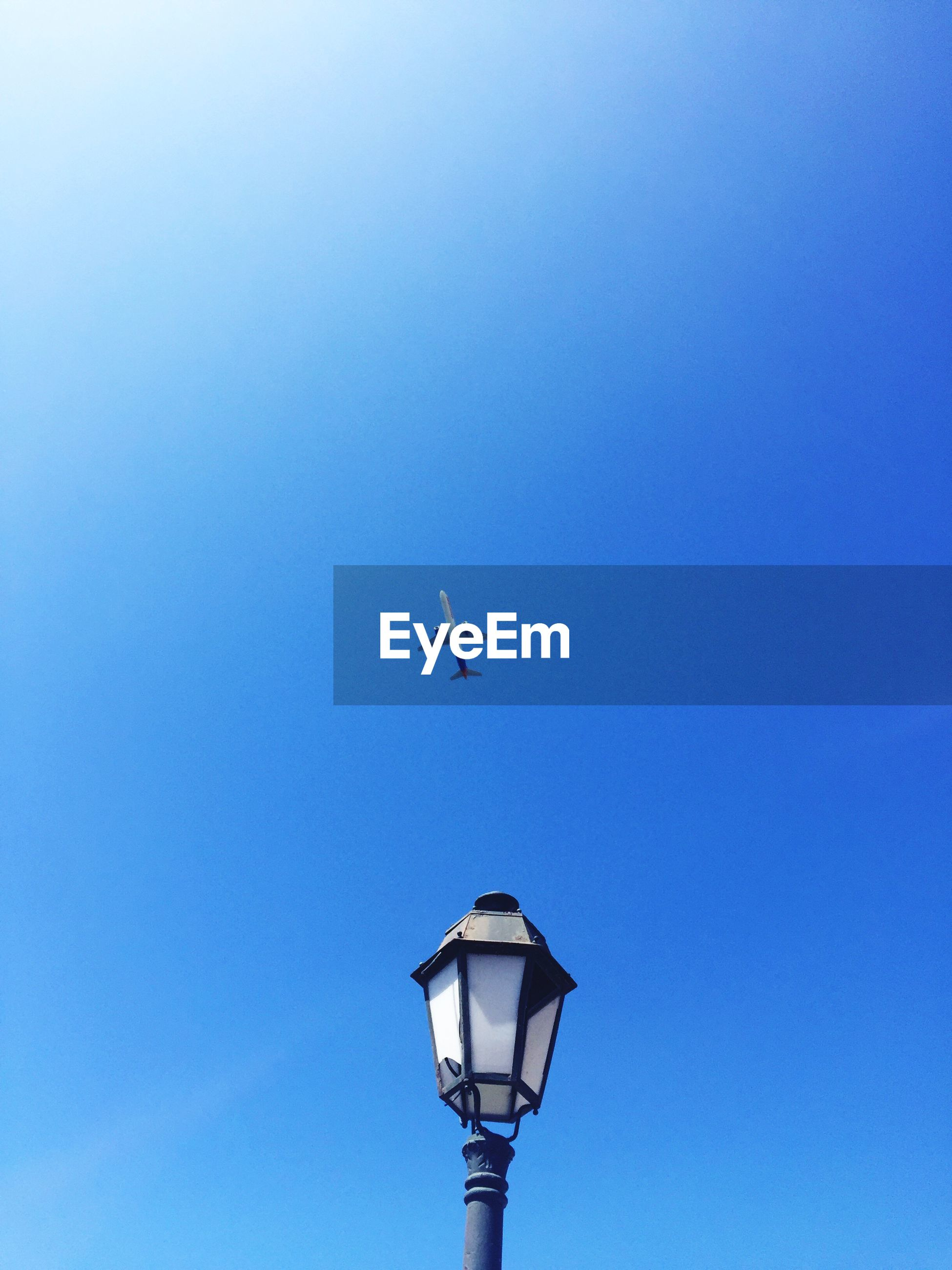 Low angle view of airplane flying over lamp post against clear blue sky