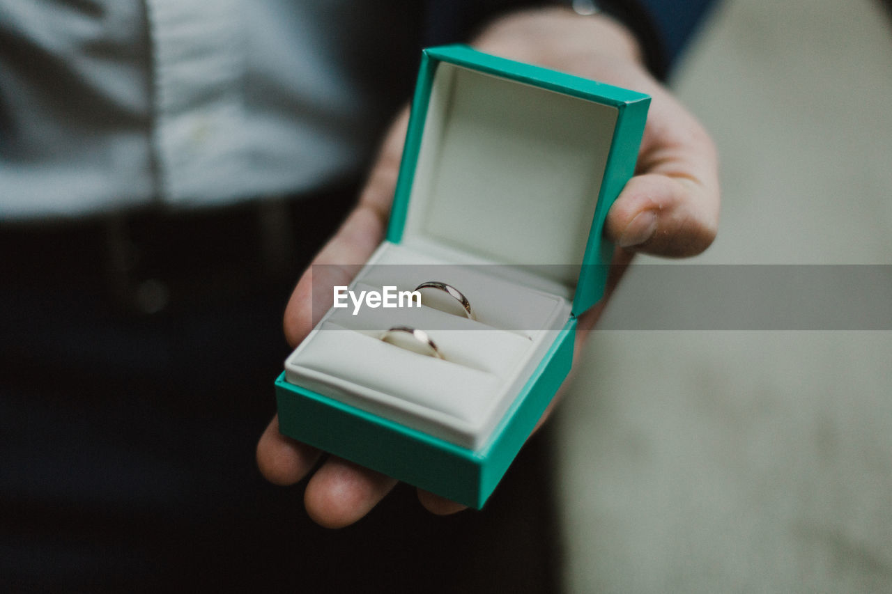 Low Section Of Groom Holding Wedding Rings While Standing Indoors