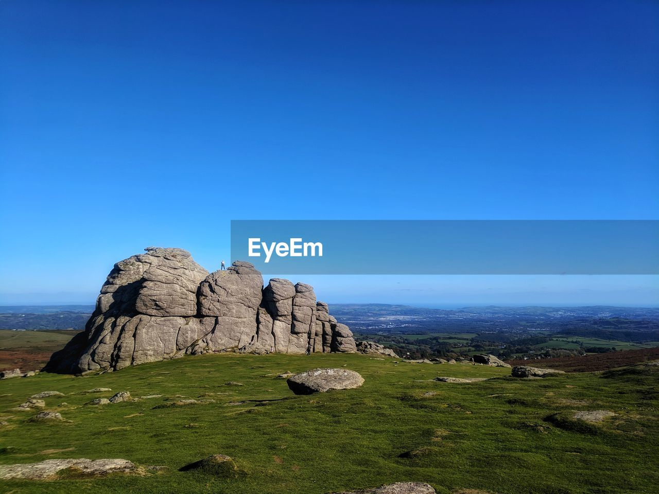sky, rock, blue, scenics - nature, tranquil scene, rock - object, solid, beauty in nature, environment, tranquility, landscape, copy space, nature, grass, rock formation, clear sky, non-urban scene, plant, day, no people, outdoors, arid climate, eroded