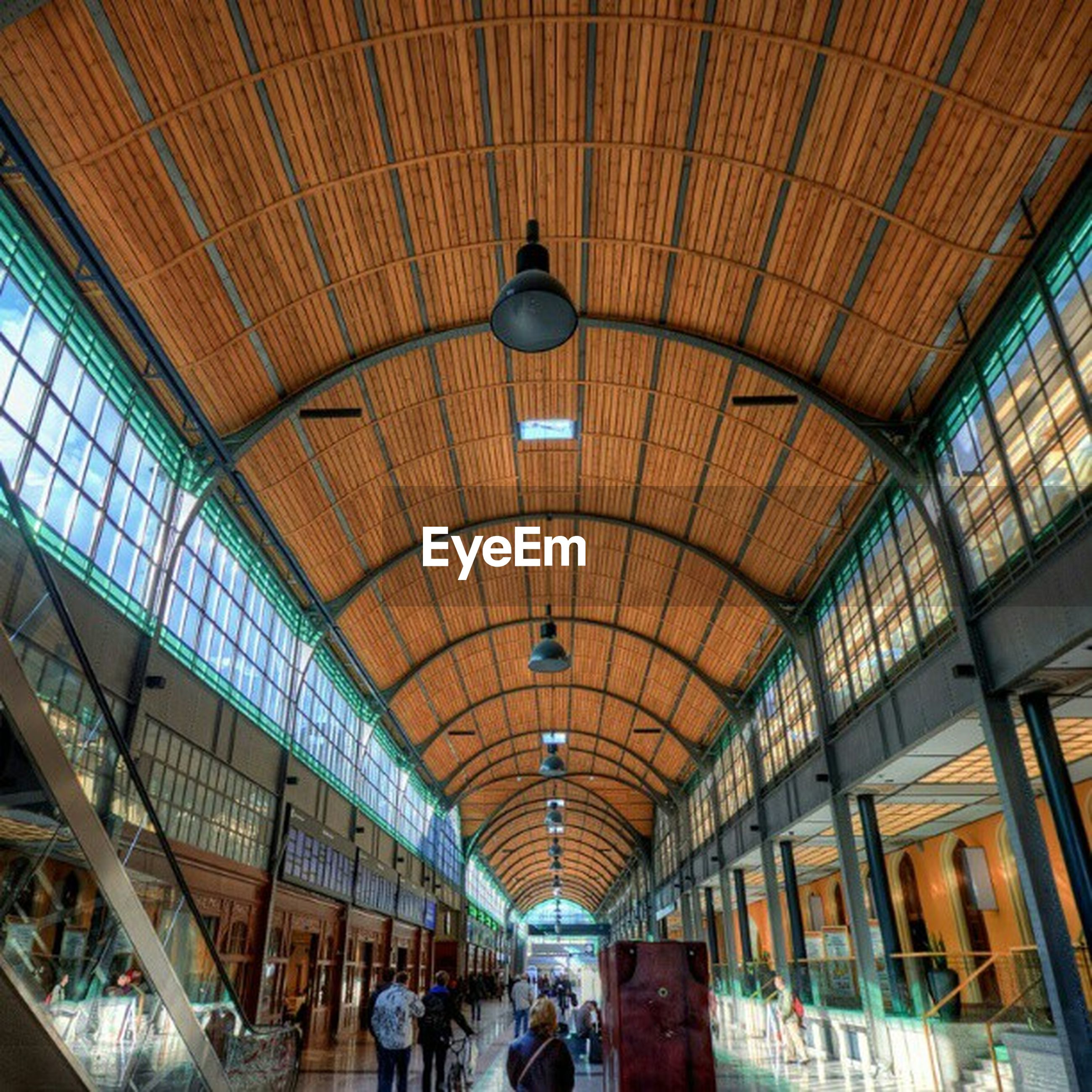 indoors, ceiling, architecture, built structure, lighting equipment, illuminated, interior, low angle view, hanging, arch, chandelier, corridor, diminishing perspective, in a row, window, incidental people, shopping mall, electric lamp, architectural feature, electric light