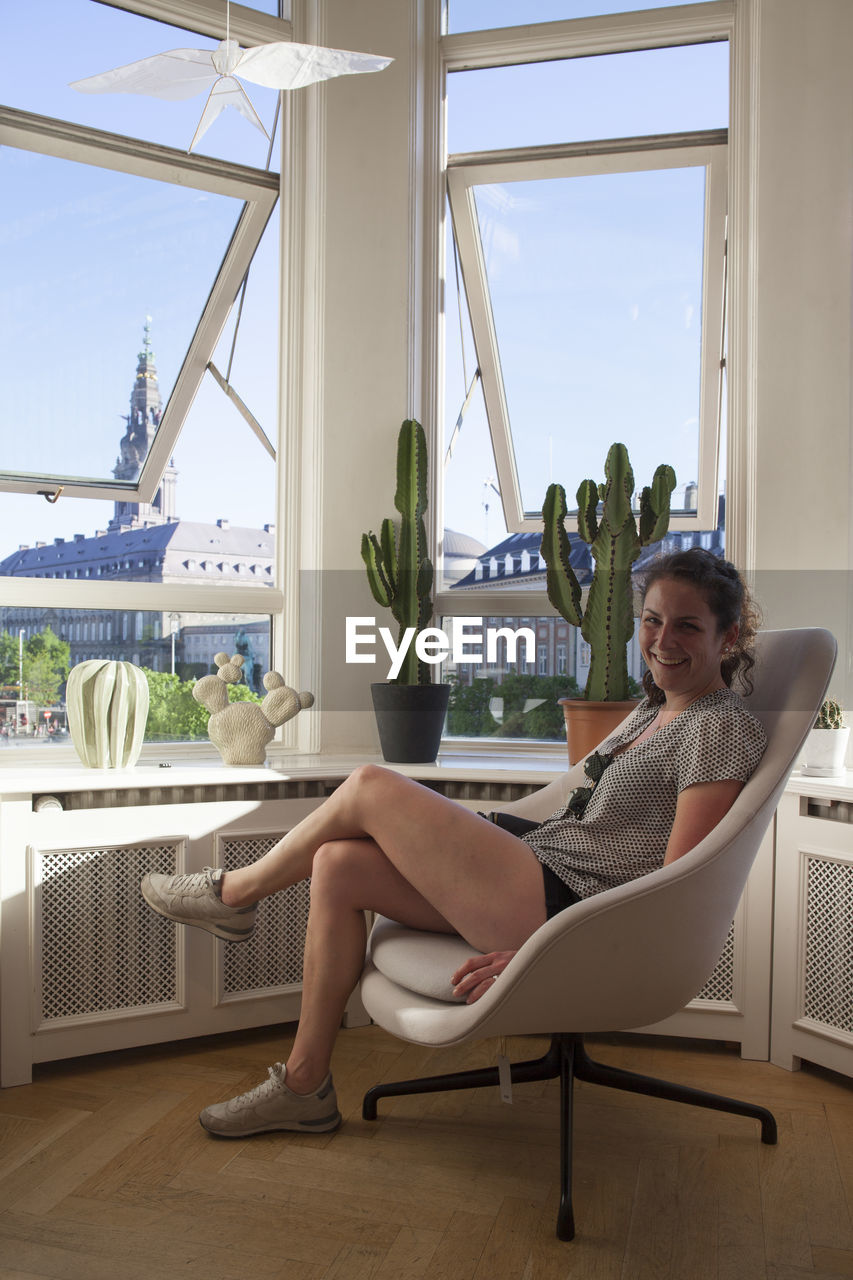 Portrait Of Smiling Woman Sitting On Chair By Windows At Home