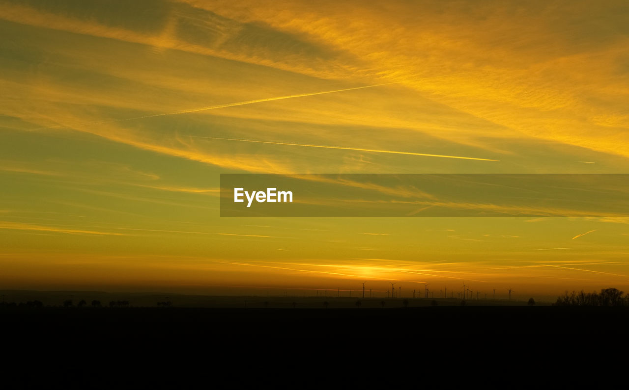 sunset, sky, beauty in nature, scenics - nature, orange color, silhouette, tranquil scene, tranquility, cloud - sky, environment, idyllic, no people, landscape, nature, yellow, non-urban scene, outdoors, dramatic sky, majestic, land, vapor trail