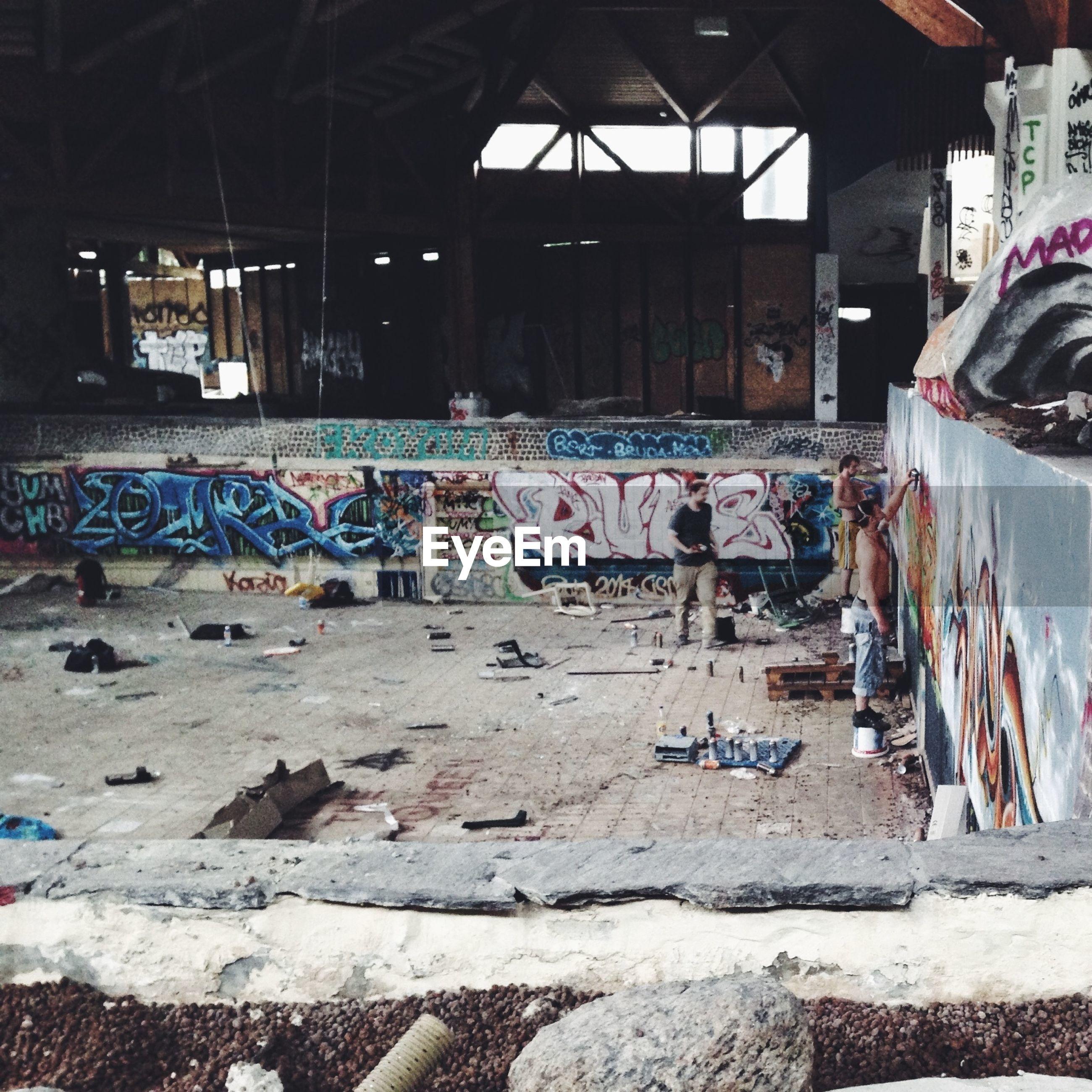 Men painting graffiti in abandoned building