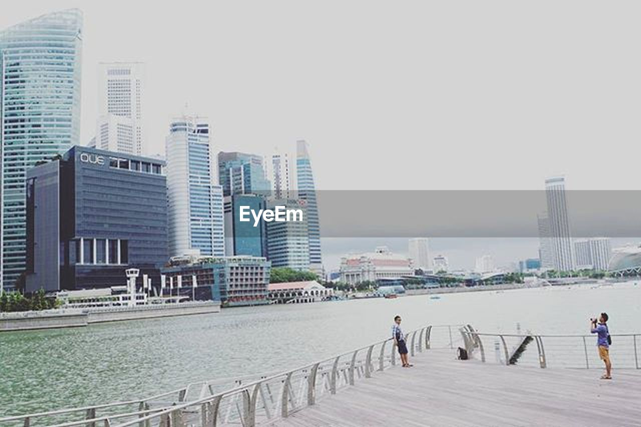 skyscraper, city, architecture, urban skyline, cityscape, downtown district, built structure, walking, city life, building exterior, bridge - man made structure, men, outdoors, water, sea, people, beach, day, adults only, full length, sky, adult, modern, clear sky, apartment, only men