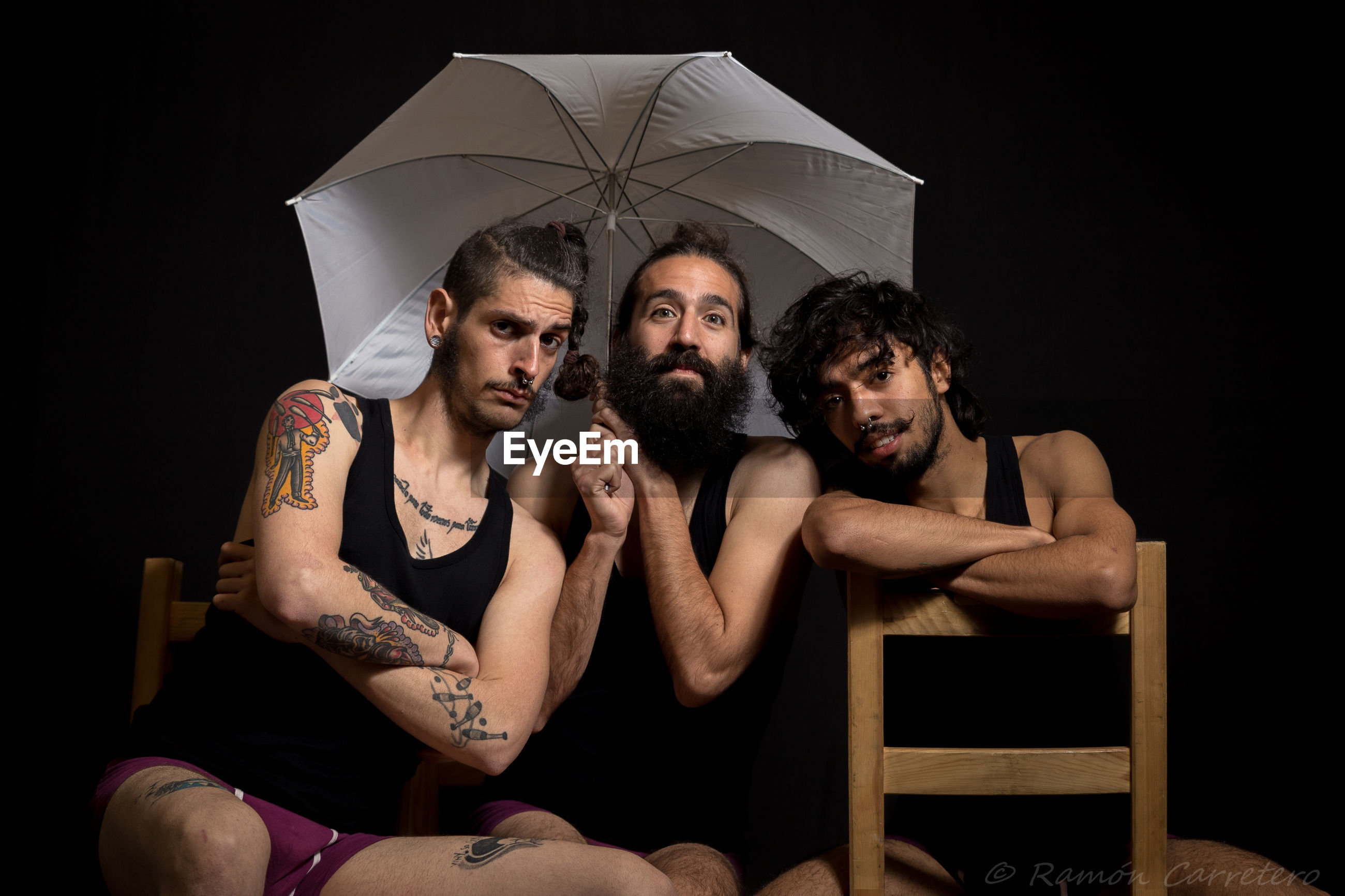 Portrait of friends sitting with umbrella against black background