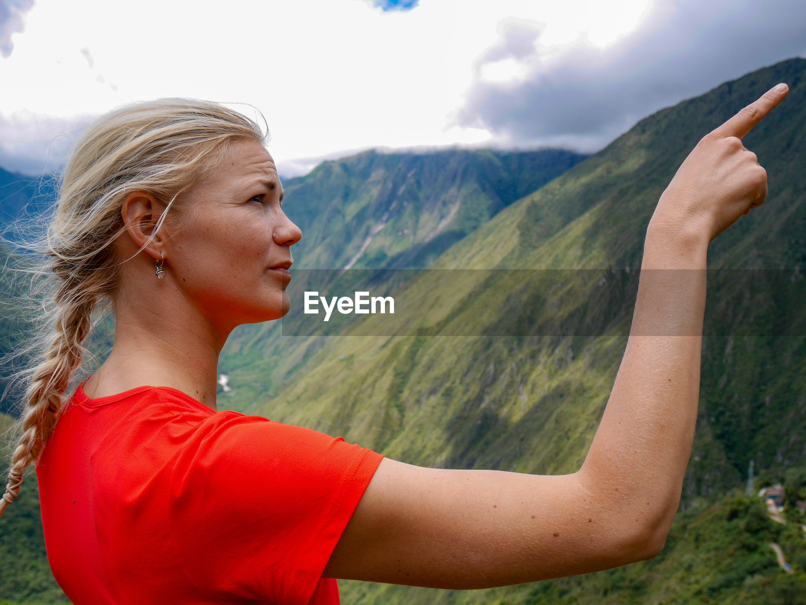 Side view of young woman pointing while standing on mountain against cloudy sky