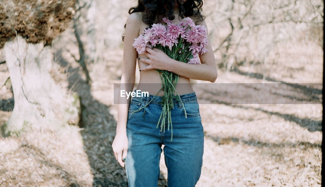Midsection Of Topless Woman Holding Bouquet