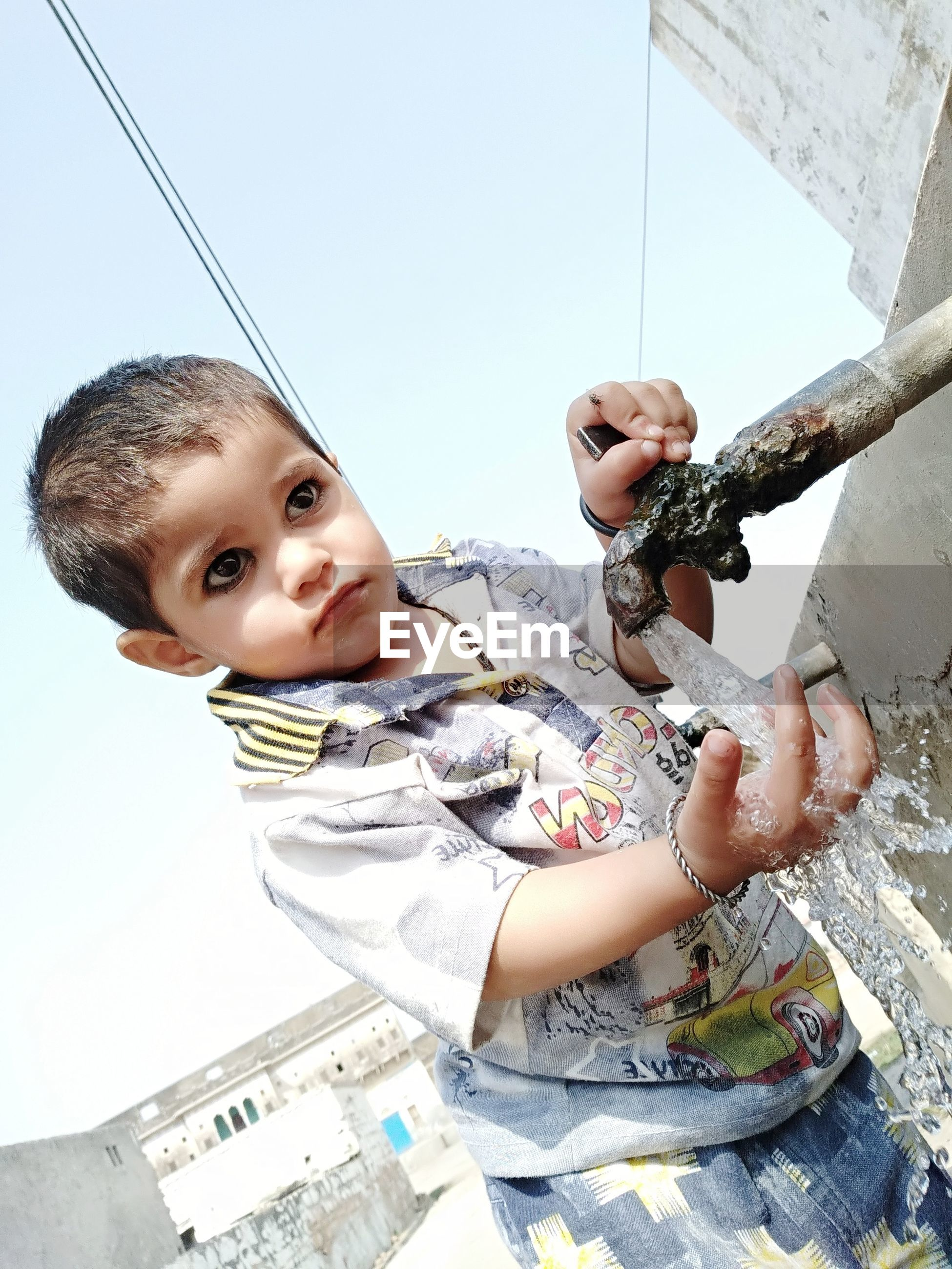 Boy standing by faucet