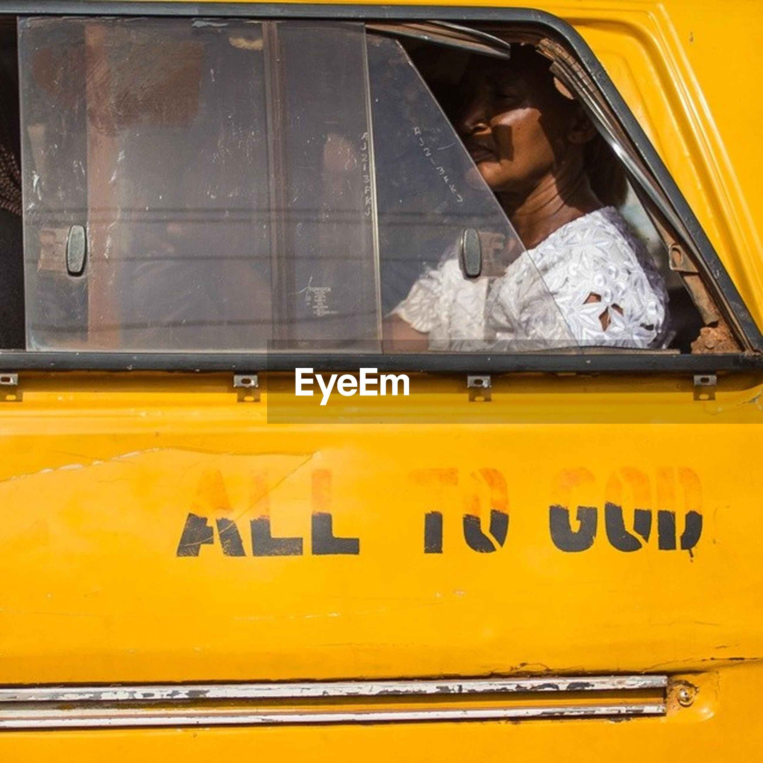 yellow, text, communication, western script, transportation, mode of transport, lifestyles, human representation, window, wall - building feature, sign, land vehicle, front view, outdoors, travel, non-western script, information sign, public transportation