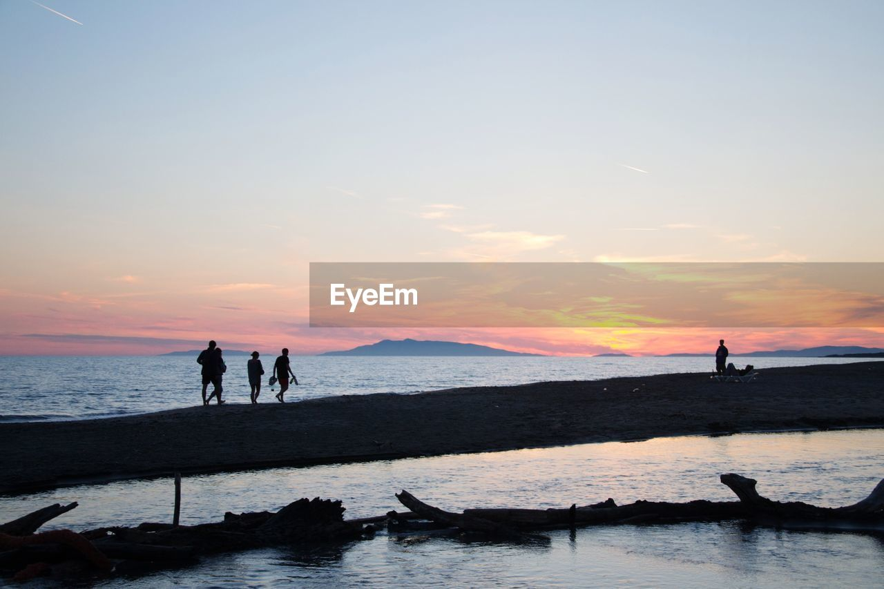 sky, water, sunset, sea, silhouette, group of people, scenics - nature, beauty in nature, cloud - sky, real people, beach, land, leisure activity, nature, orange color, lifestyles, men, people, standing, horizon over water, outdoors