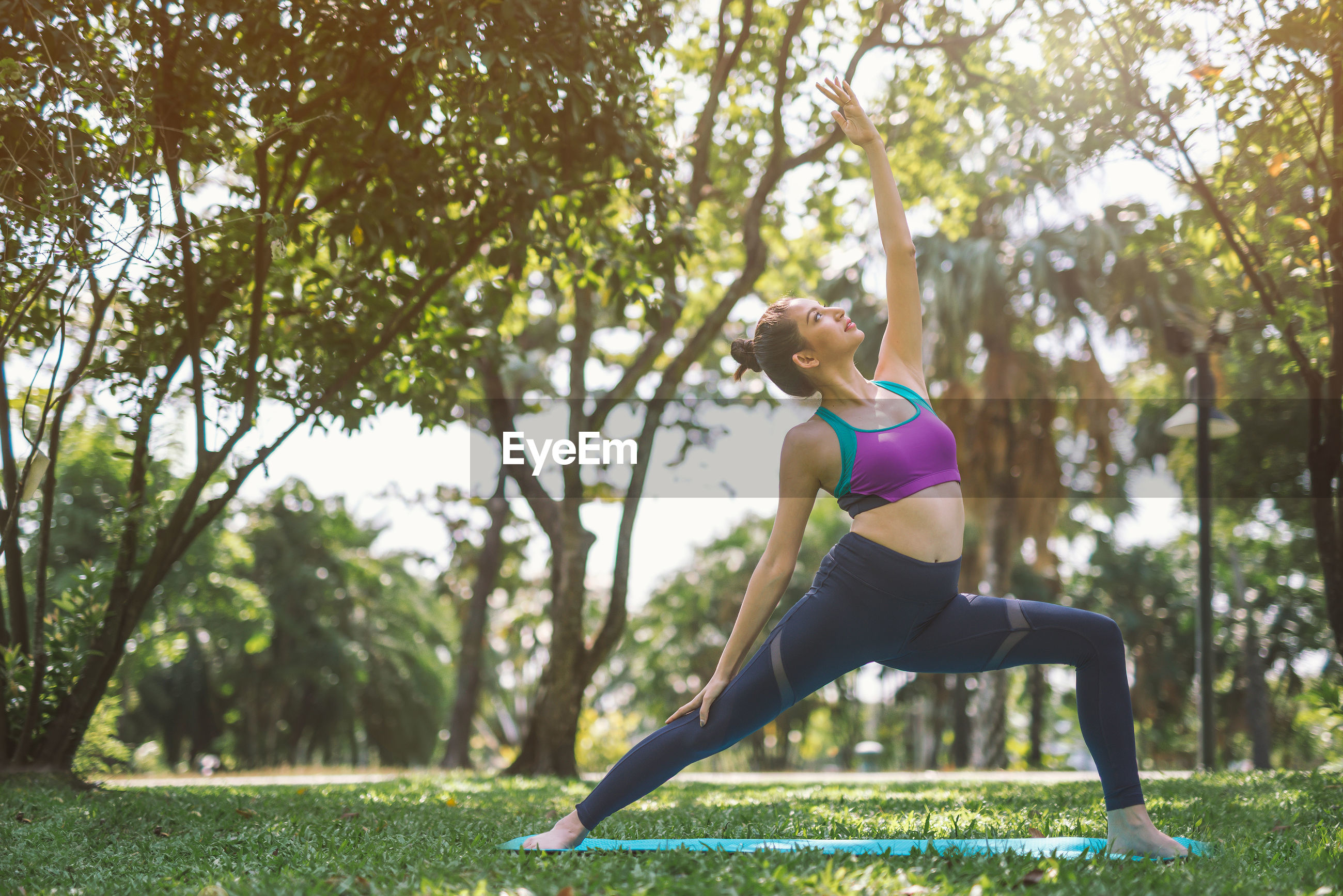 Full length of young woman exercising at park