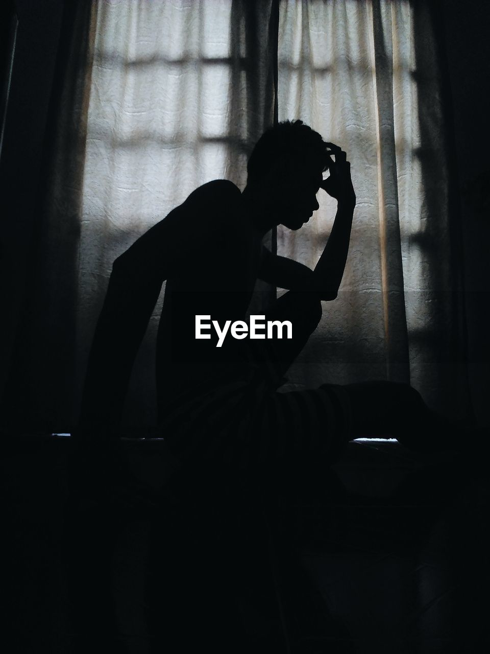 Silhouette Of Young Man Sitting At Home