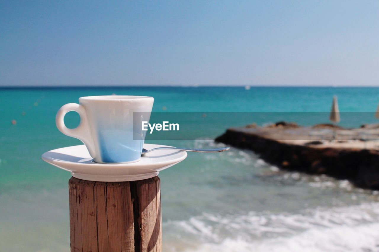 Close-up of coffee cup on wooden post at beach against sky