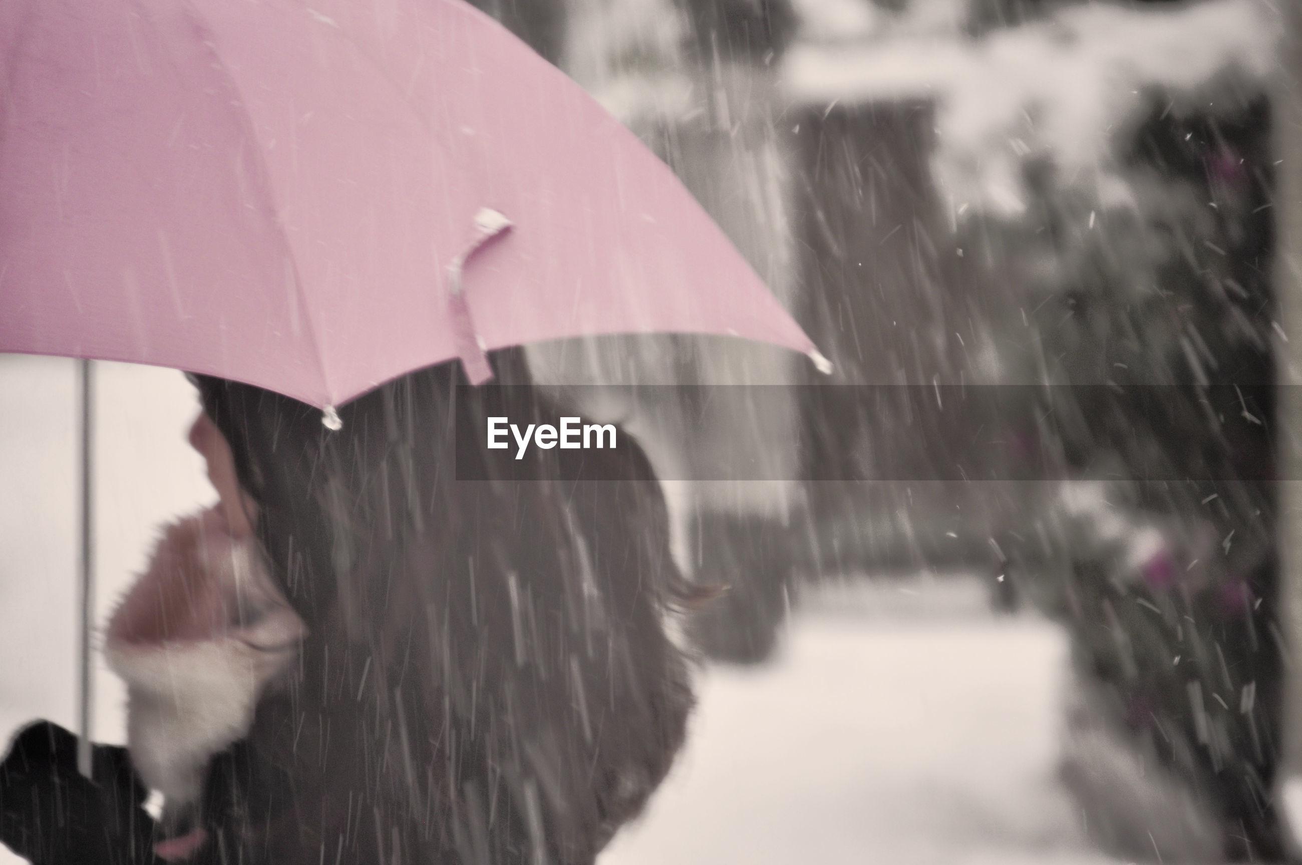 Woman holding umbrella during snow