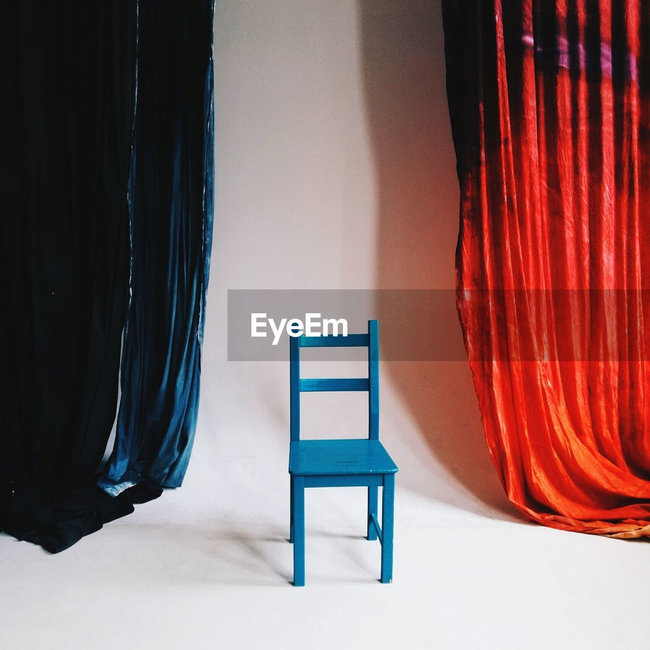 curtain, seat, empty, indoors, absence, chair, no people, red, textile, home interior, wall - building feature, day, architecture, stage, relaxation, orange color, furniture, stage - performance space, armchair, shadow