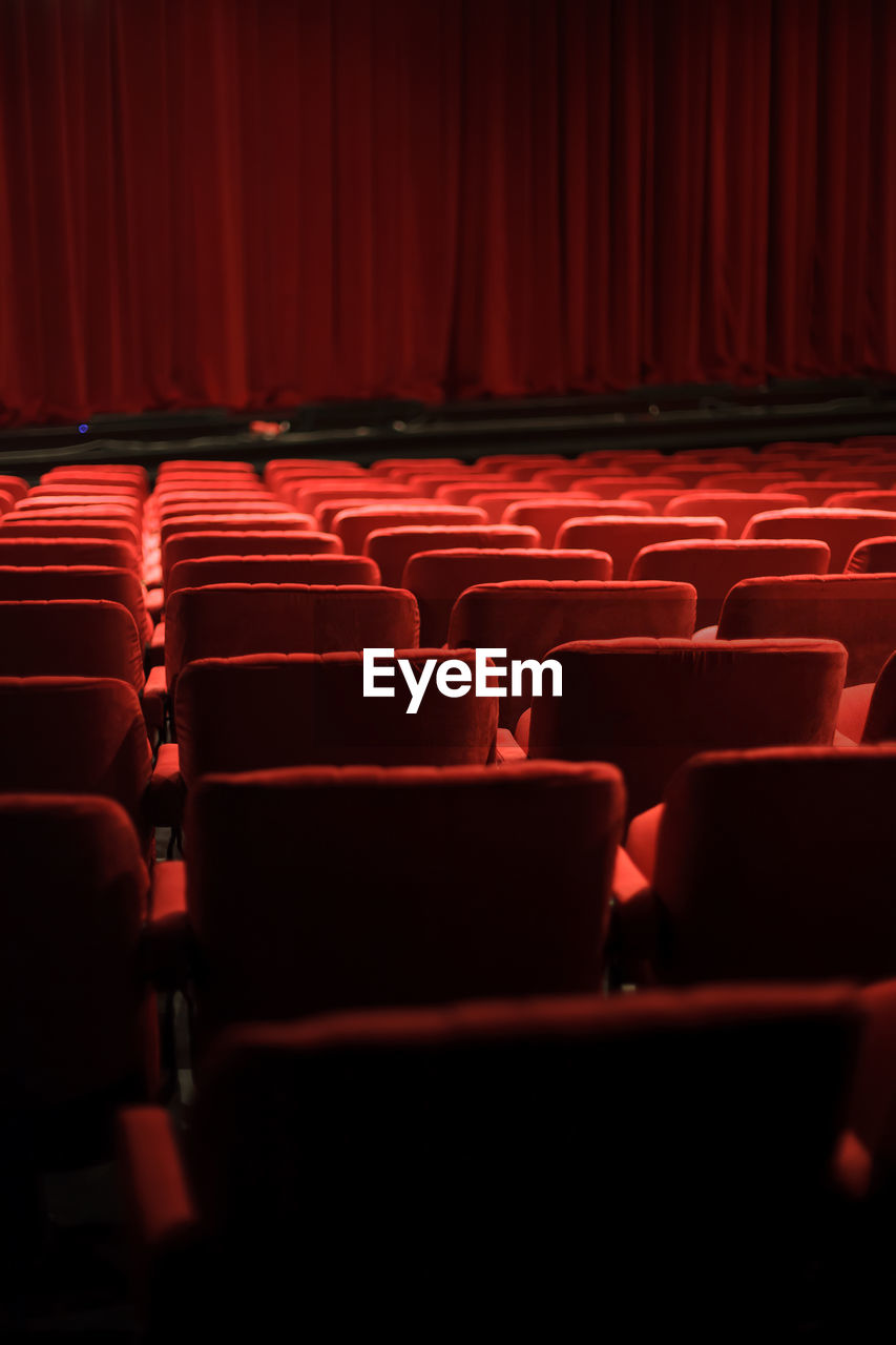 red, in a row, arts culture and entertainment, seat, movie theater, indoors, empty, absence, no people, chair, repetition, film industry, theater, side by side, order, auditorium, curtain, arrangement, stage - performance space, stage theater, stage