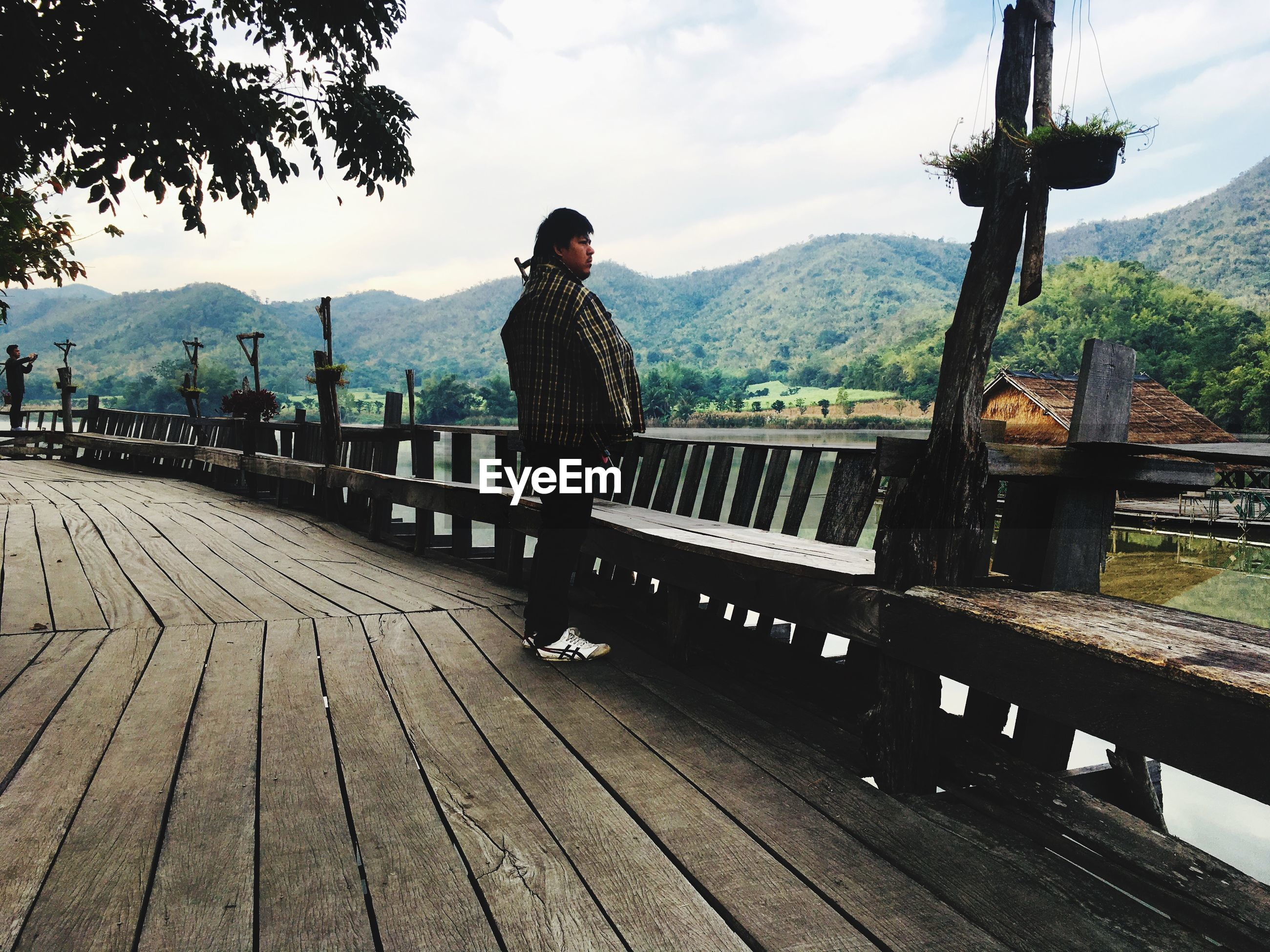 MAN STANDING ON BENCH BY RAILING AGAINST MOUNTAIN