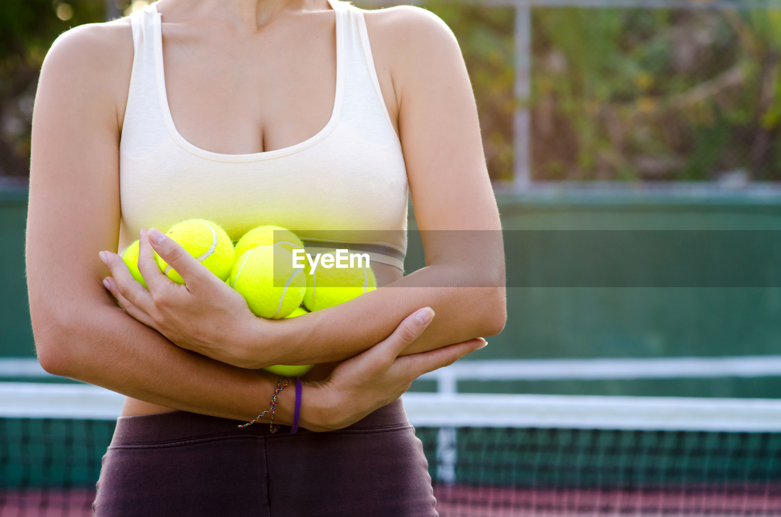 Midsection of woman holding tennis balls while standing in court