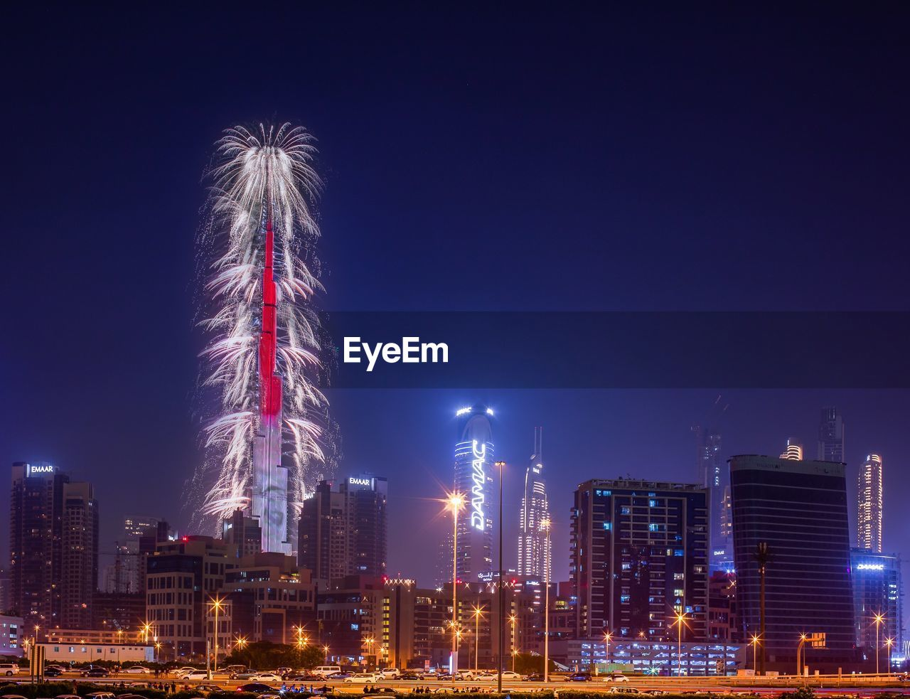 building exterior, architecture, illuminated, night, built structure, sky, city, tall - high, skyscraper, office building exterior, cityscape, building, tower, urban skyline, landscape, nature, no people, motion, glowing, long exposure, outdoors, firework, modern, financial district, firework display, light, firework - man made object, spire