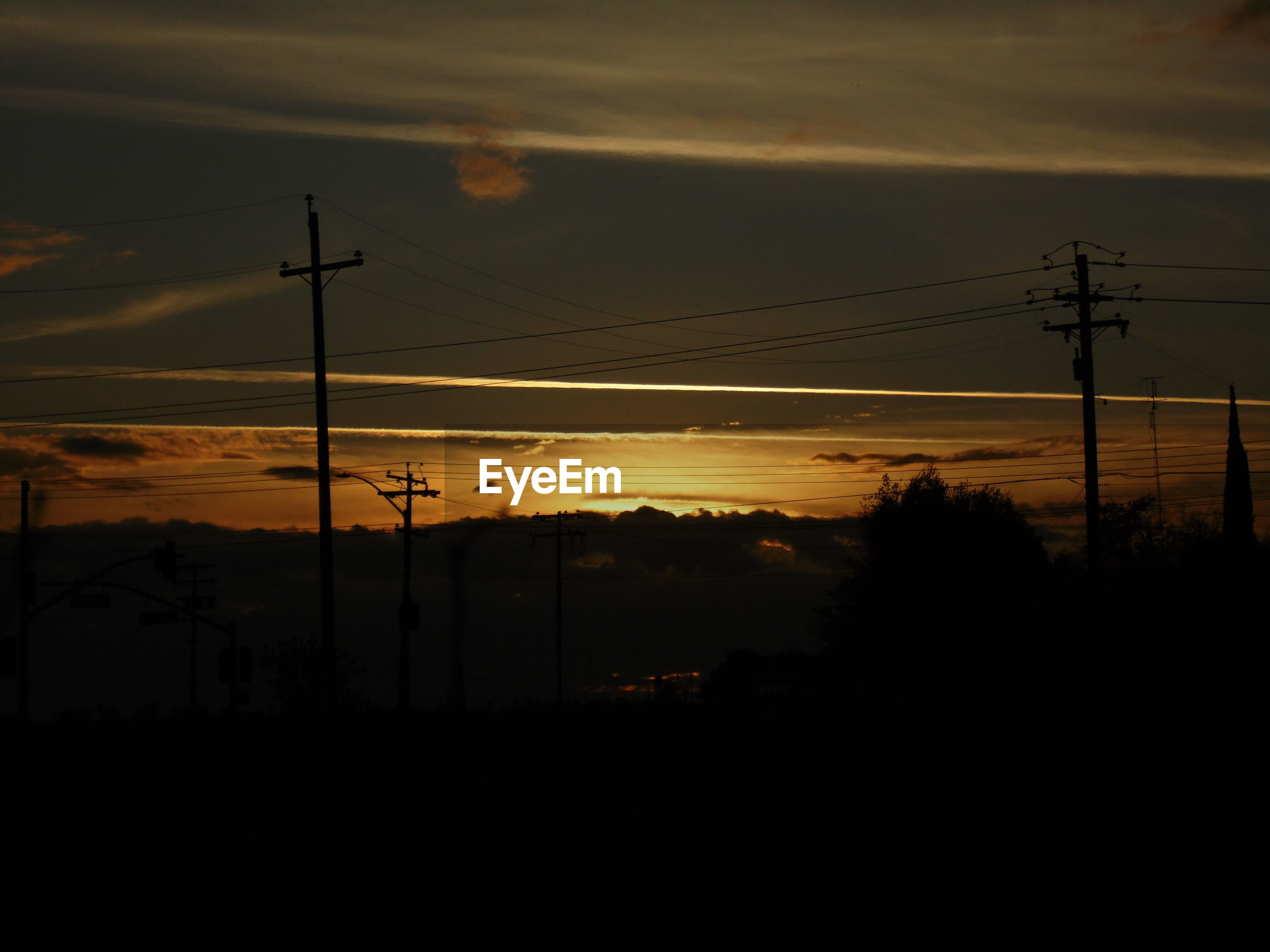 Silhouette electricity pylons against cloudy sky during sunset