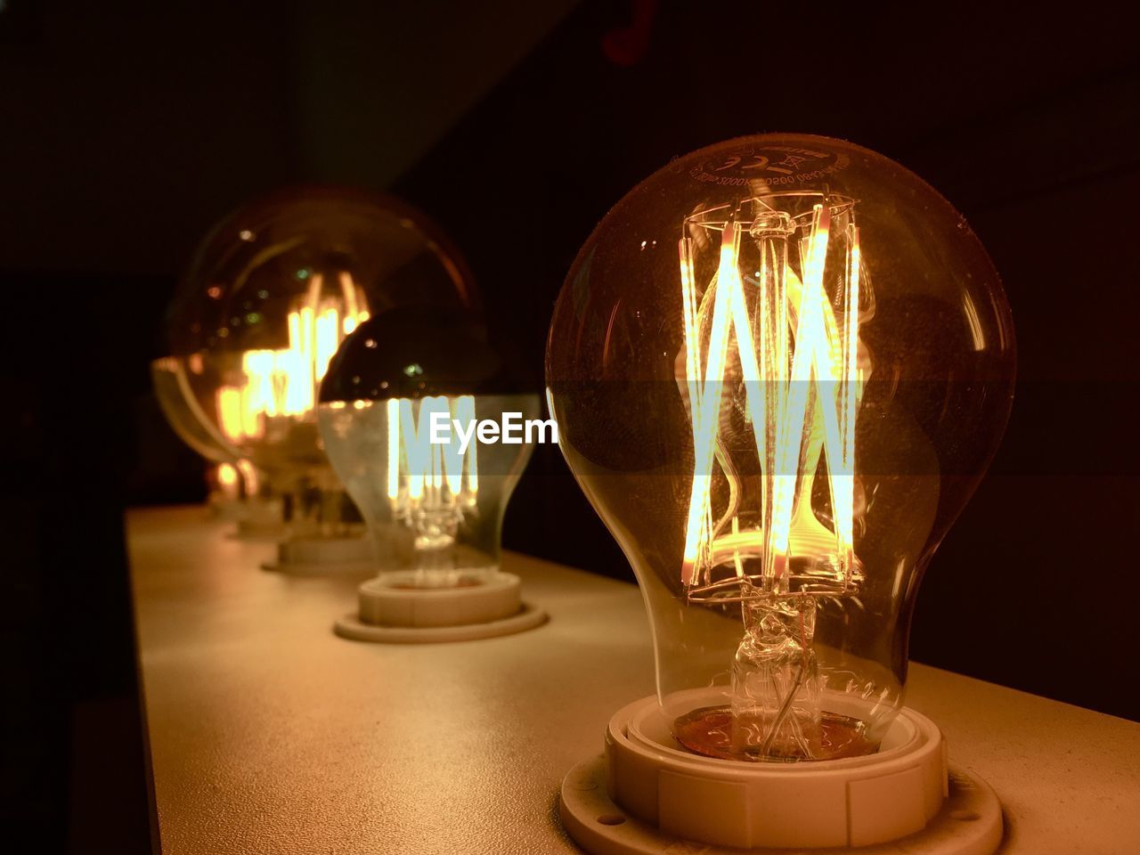 illuminated, lighting equipment, electricity, light bulb, table, filament, indoors, no people, close-up, technology