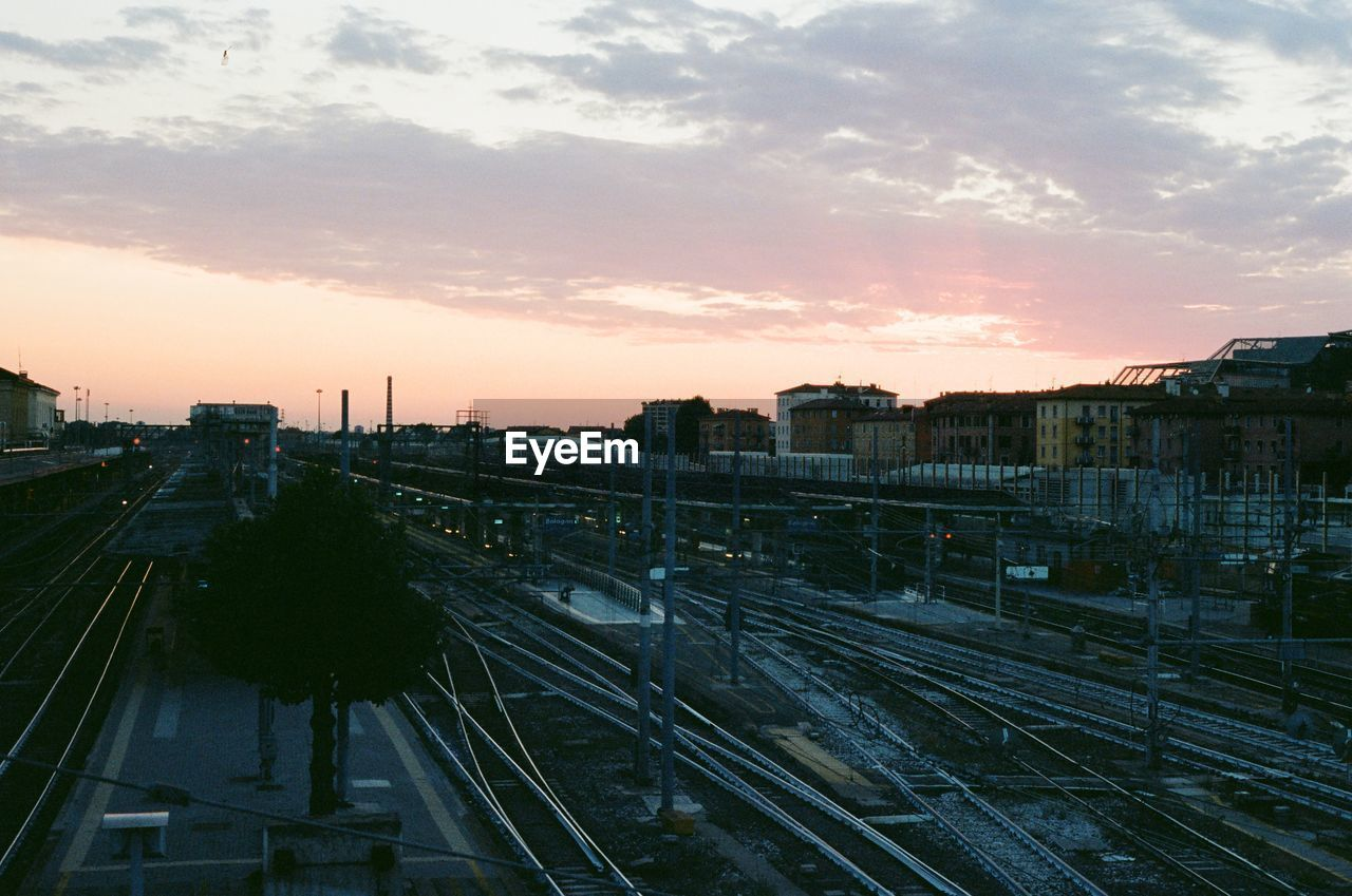 rail transportation, sky, track, building exterior, built structure, architecture, sunset, cloud - sky, railroad track, city, train, transportation, high angle view, train - vehicle, mode of transportation, public transportation, no people, nature, railroad station, cityscape, outdoors, shunting yard