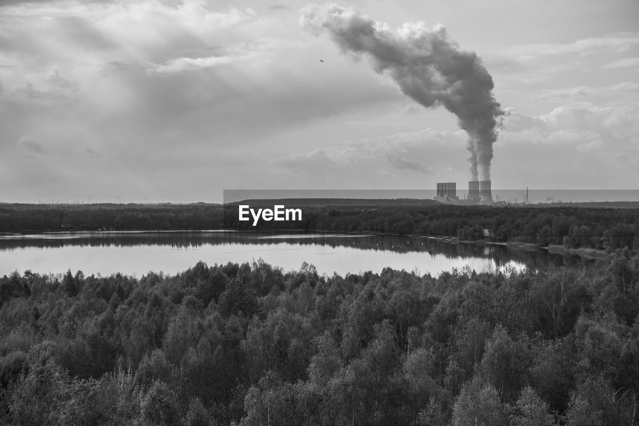 Smoke Emitting From Factory By Lake Against Sky