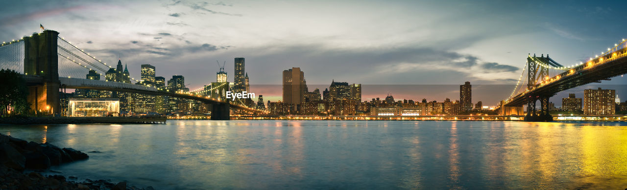 Panoramic View Of Illuminated Suspension Bridges And Manhattan Skyline