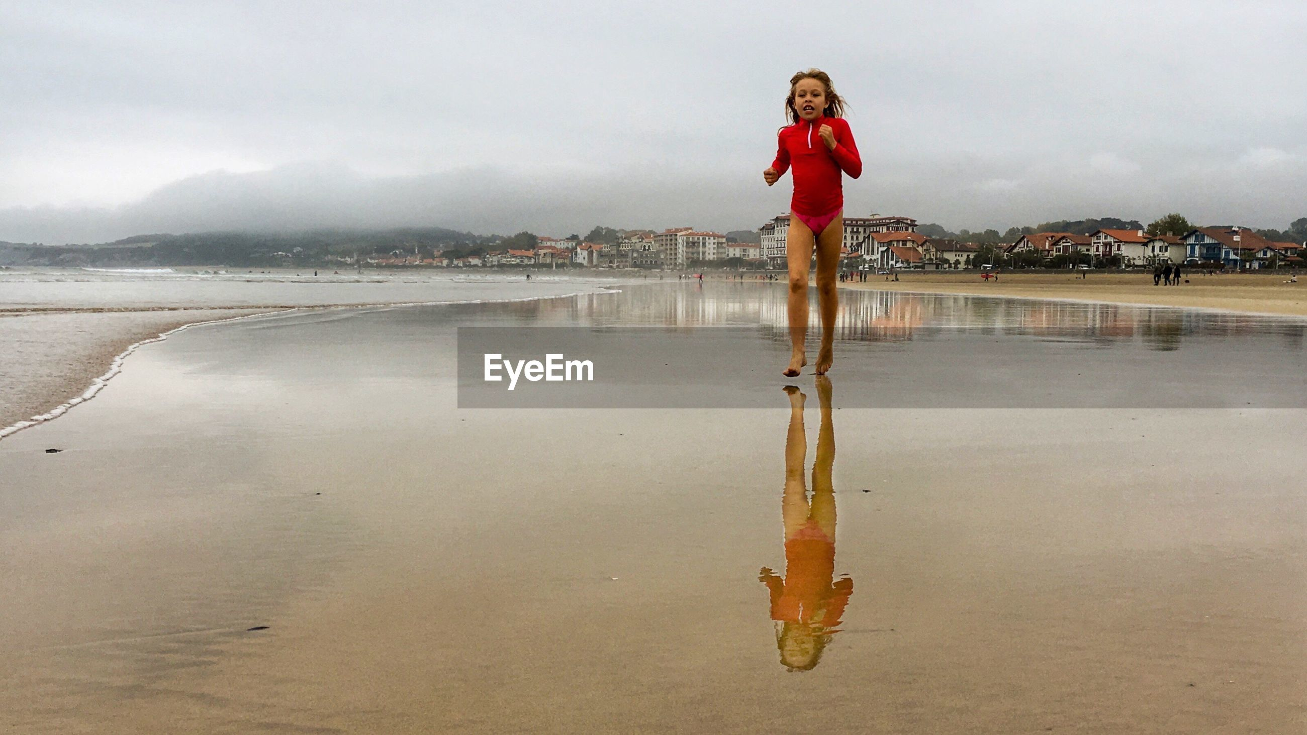 Girl running on shore at beach against sky