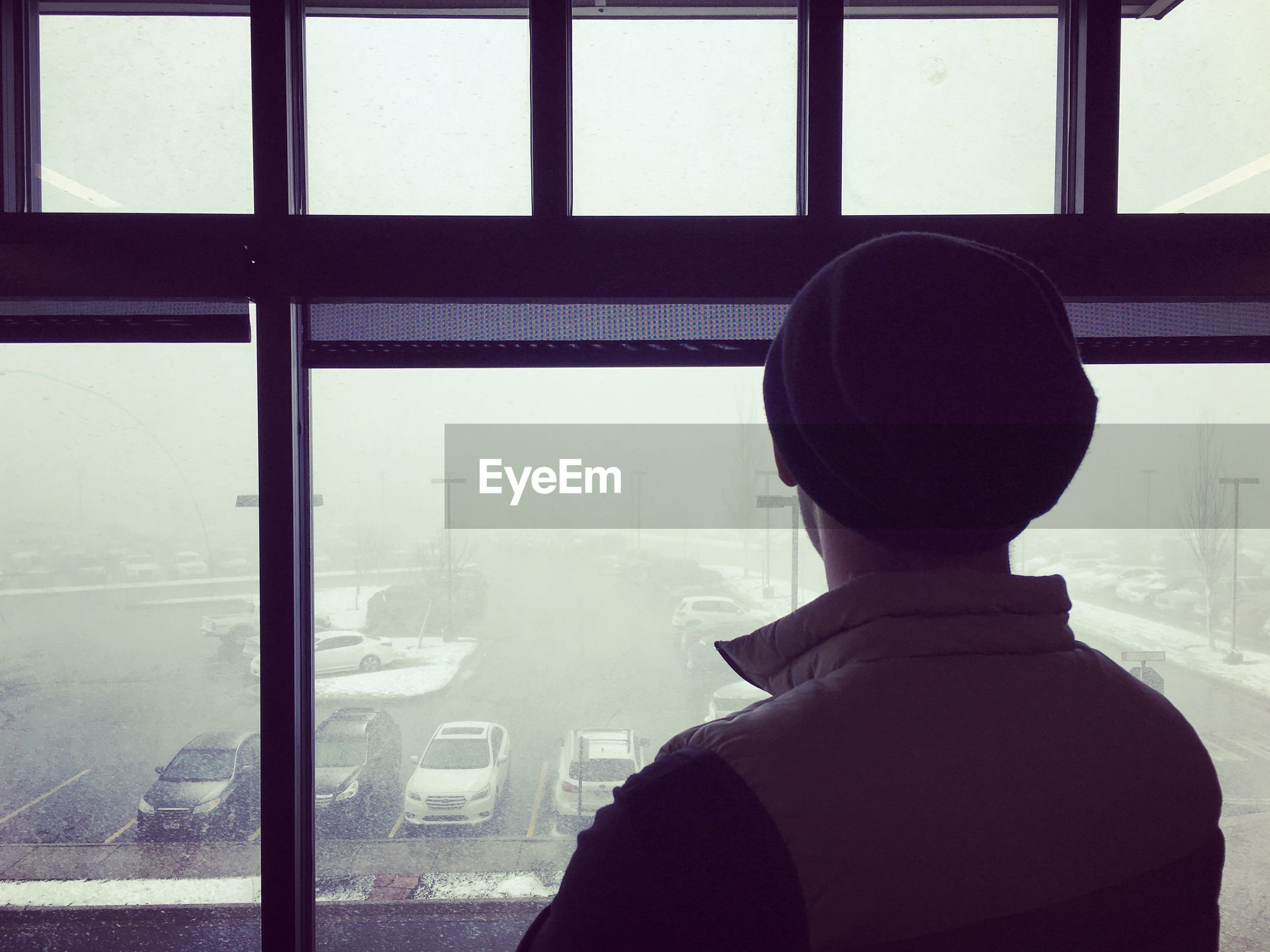 window, glass - material, real people, transparent, one person, headshot, rear view, looking, lifestyles, indoors, day, portrait, men, transportation, mode of transportation, public transportation, airplane, looking through window, standing, looking at view