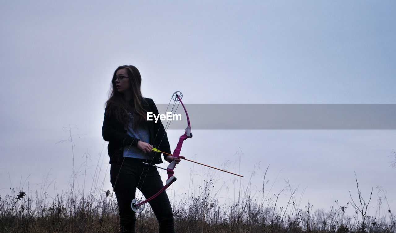 Woman Practicing Archery Against Sky
