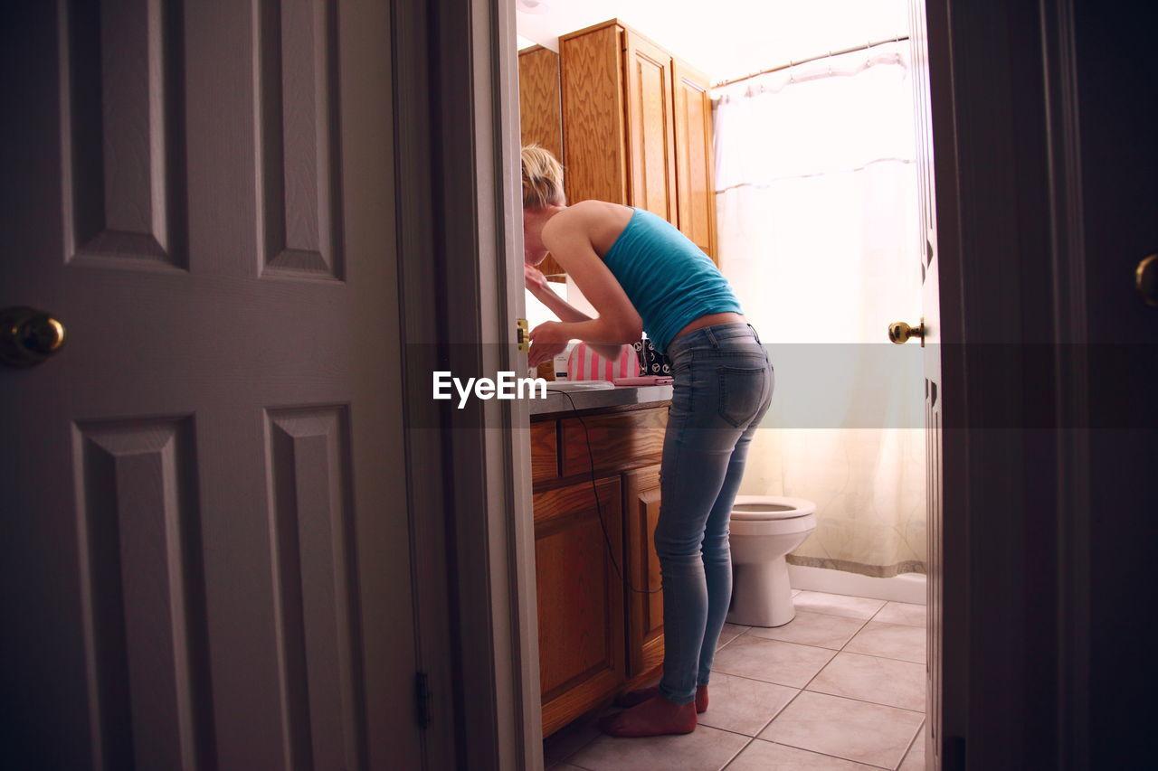 Woman standing in bathroom seen through open door at home
