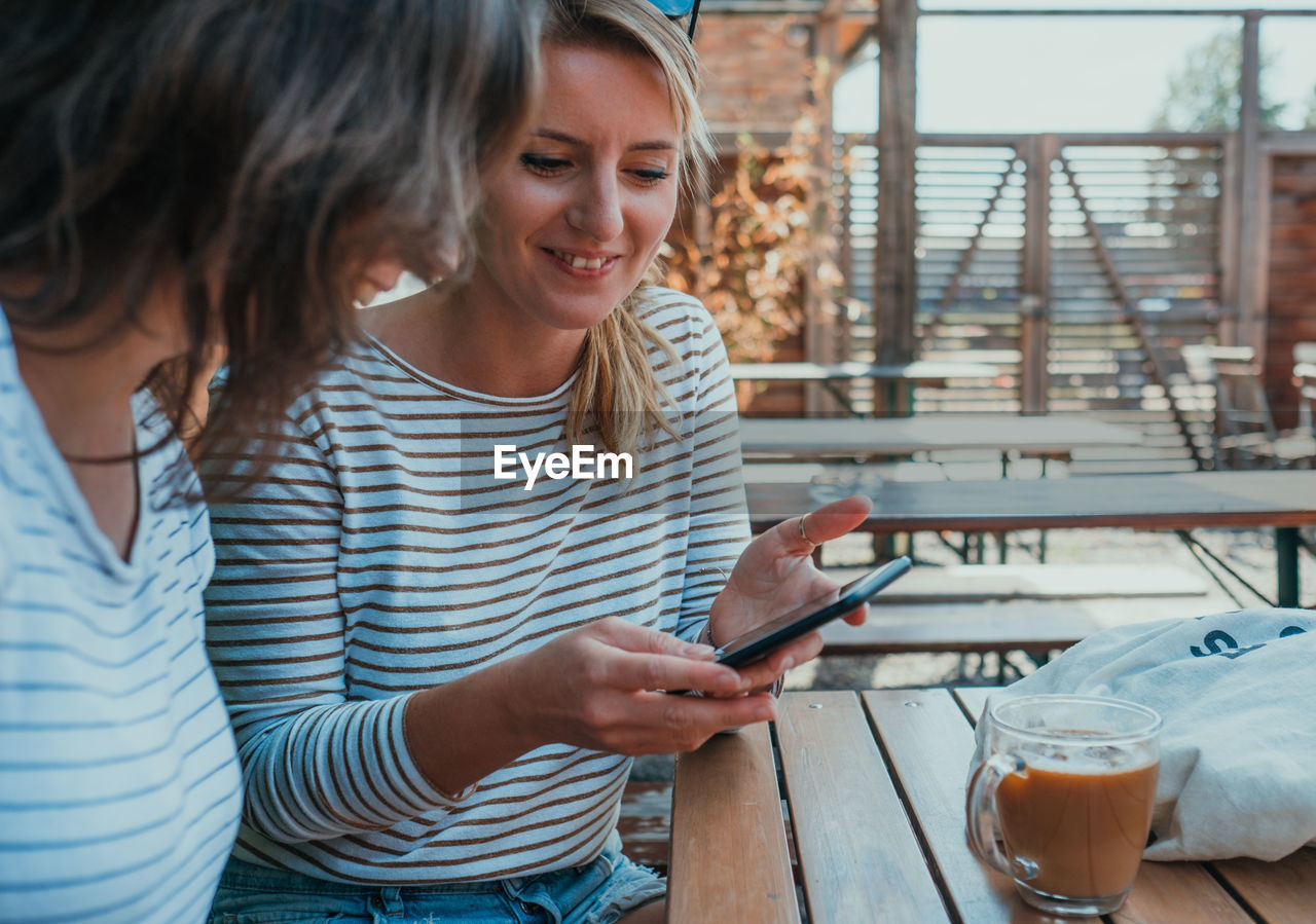 Female friends looking in smart phone at table